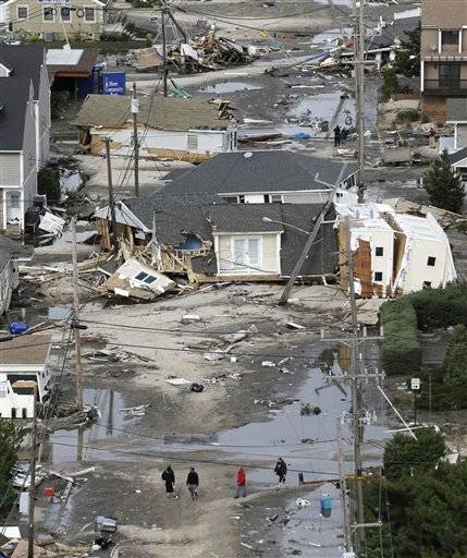 In this aerial photo, people walk amid the destruction left in the wake of superstorm Sandy, Wednesday, Oct. 31, 2012, in Seaside Heights, N.J.
