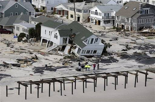 In this aerial photo, people survey destruction left in the wake of superstorm Sandy, Wednesday, Oct. 31, 2012, in Seaside Heights, N.J.