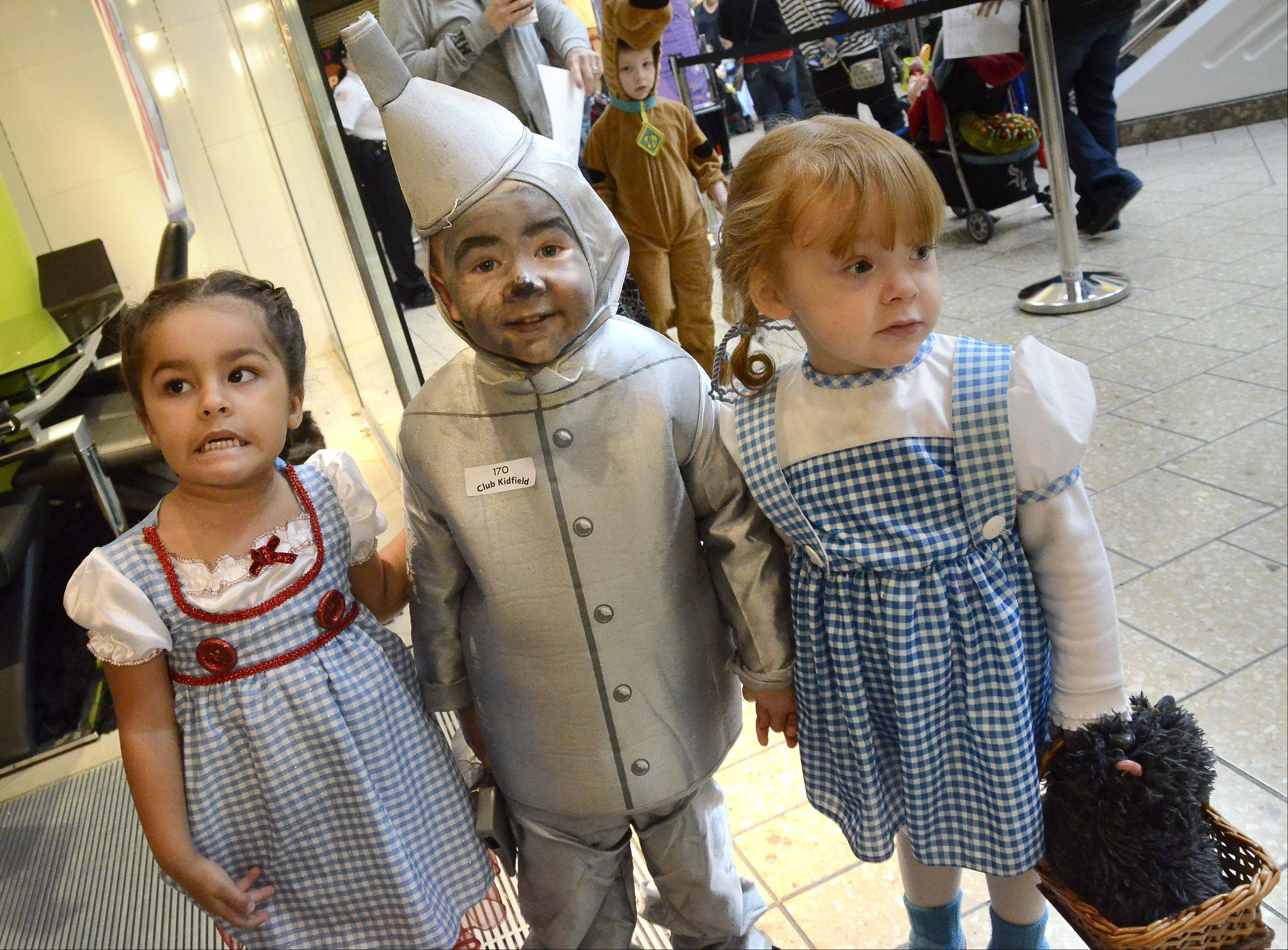 "Dressed as Dorothy from ""The Wizard of Oz,"" Peyton Hawkins, 3, of Streamwood shares Tin Man Isaac Eisenhauer, 3, of Mount Prospect, with his sister Kaleigh Eisenhauer, 2, at the Halloween Bash hosted Wednesday by the Woodfield Mall in Schaumburg."