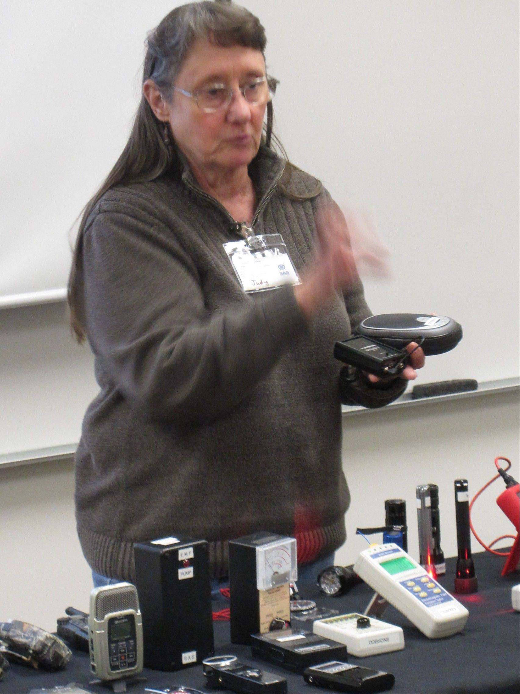 "Judy Dobson, who with her husband, Dennis, is a founding member of the Society for Anomalous Studies, shows a Ghost Box Ovilus X during the ""Investigating Ghosts and Hauntings"" Saturday at McHenry County College. The gadget is supposed to transform into words recorded changes in temperature and electromagnetic field."