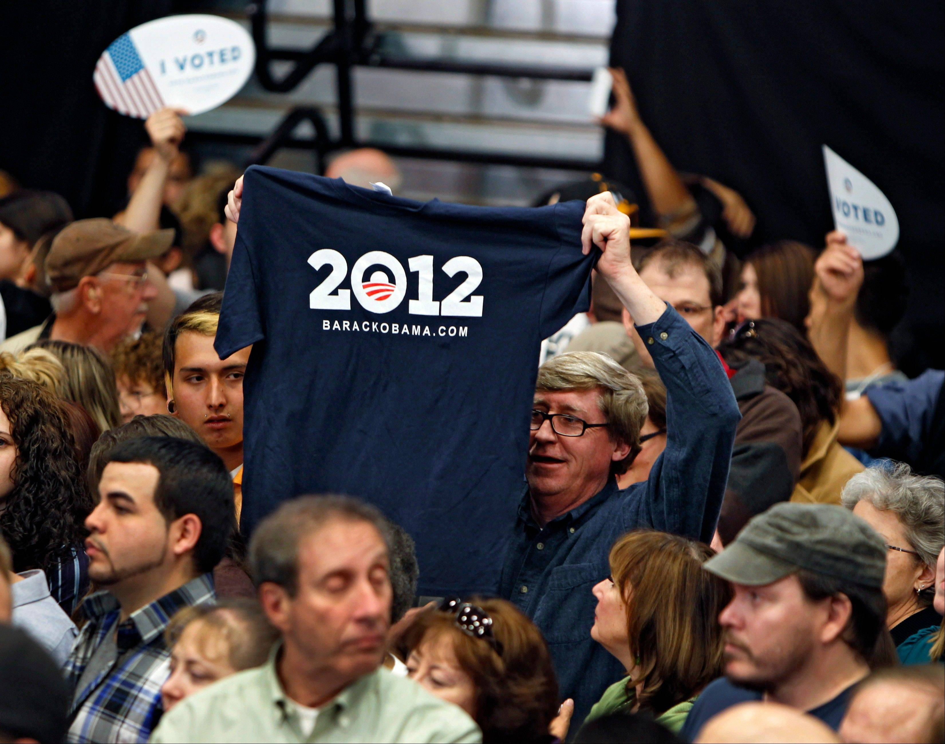 An Obama supporter holds up a 2012 shirt supporting President Barack Obama at a campaign rally at Adams City High School in Commerce City, Colo., Tuesday, Oct. 30, 2012.
