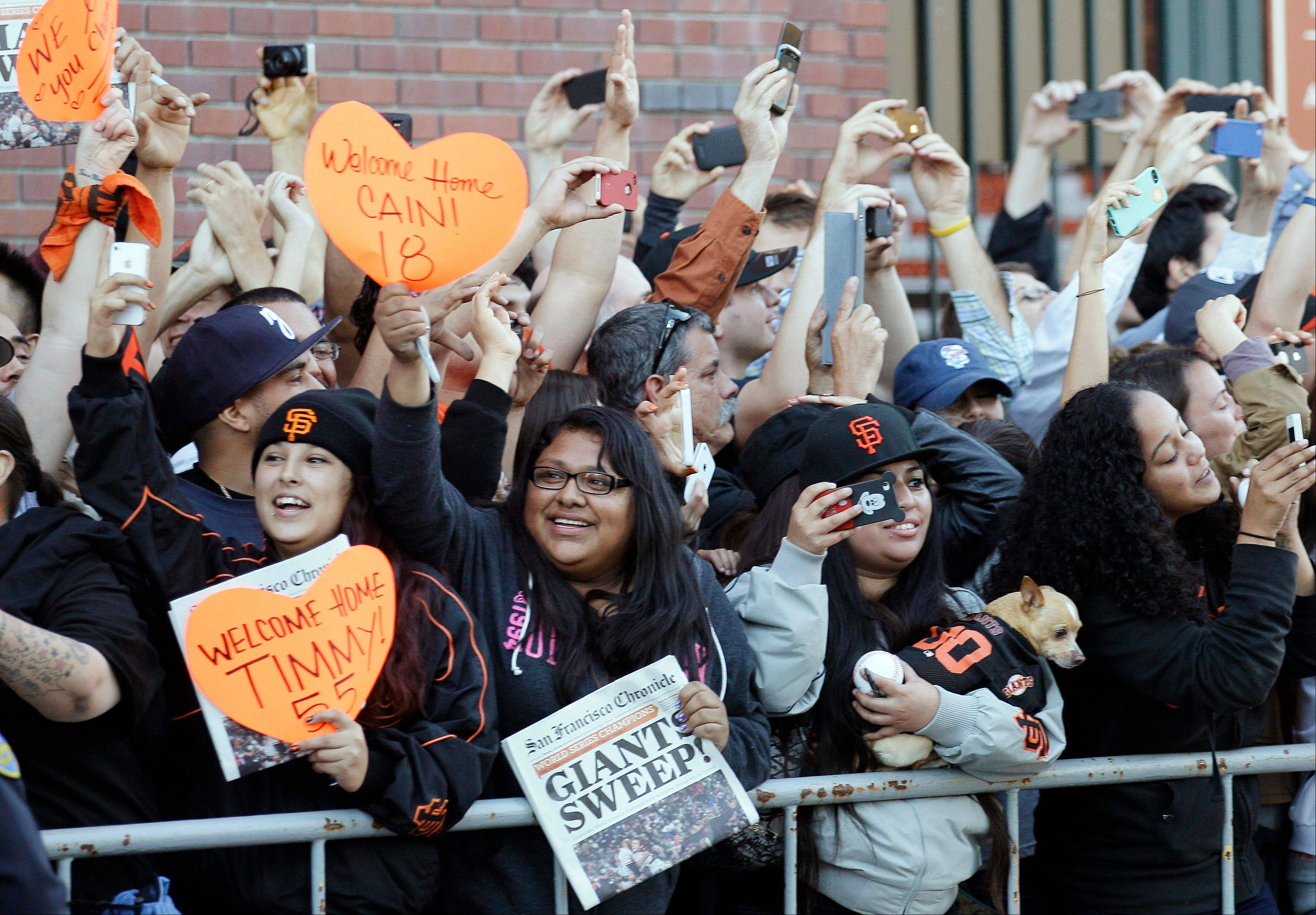 San Francisco Giants fans cheer as the team buses arrive outside of AT&T Park in San Francisco, Monday, Oct. 29, 2012. The Giants defeated the Detroit Tigers to win baseball's World Series.