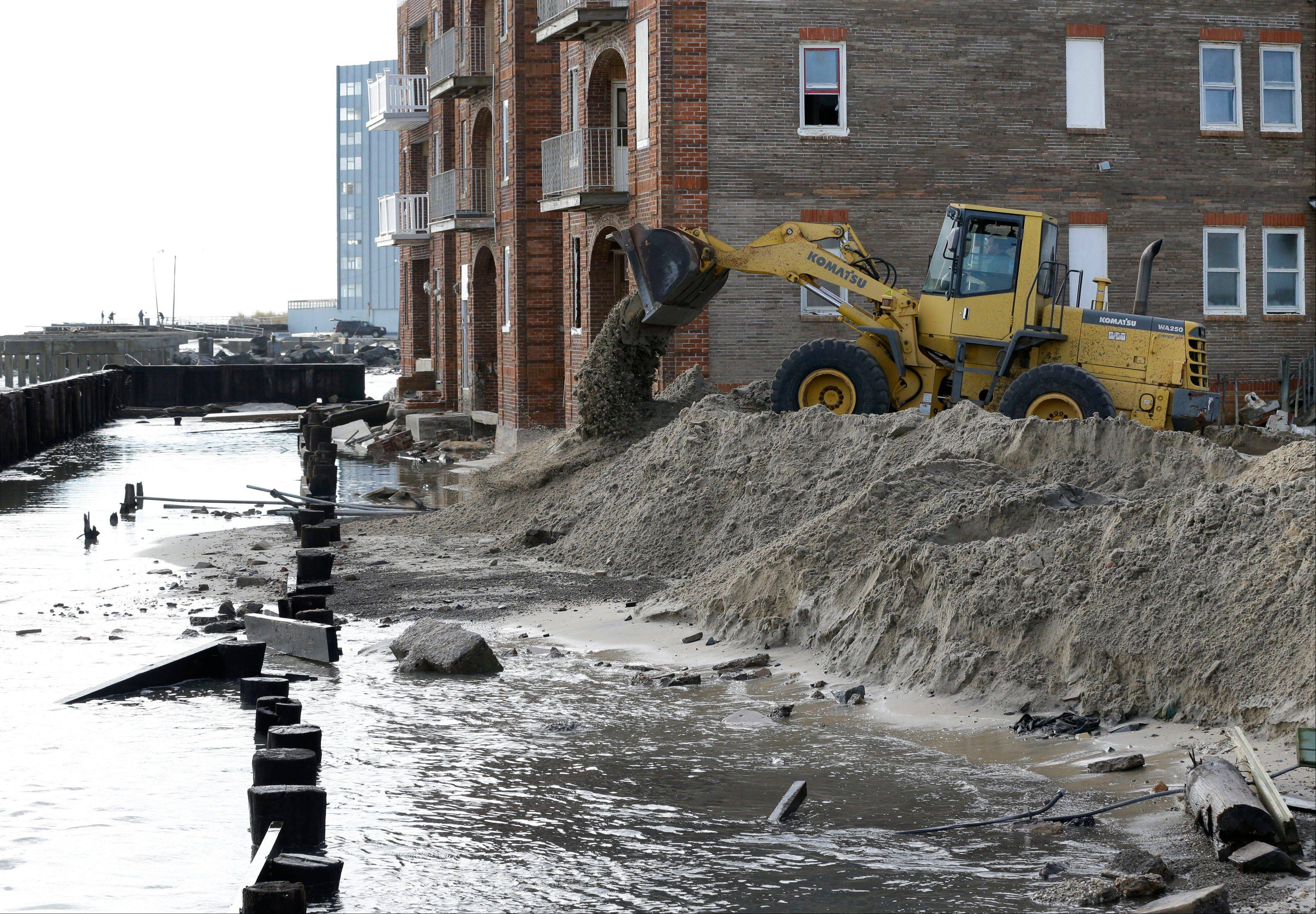 A worker uses a backhoe to move sand near a boardwalk that was destroyed by superstorm Sandy in Atlantic City, N.J., Wednesday, Oct. 31, 2012. Sandy, the storm that made landfall Monday, caused multiple fatalities, halted mass transit and cut power to more than 6 million homes and businesses.