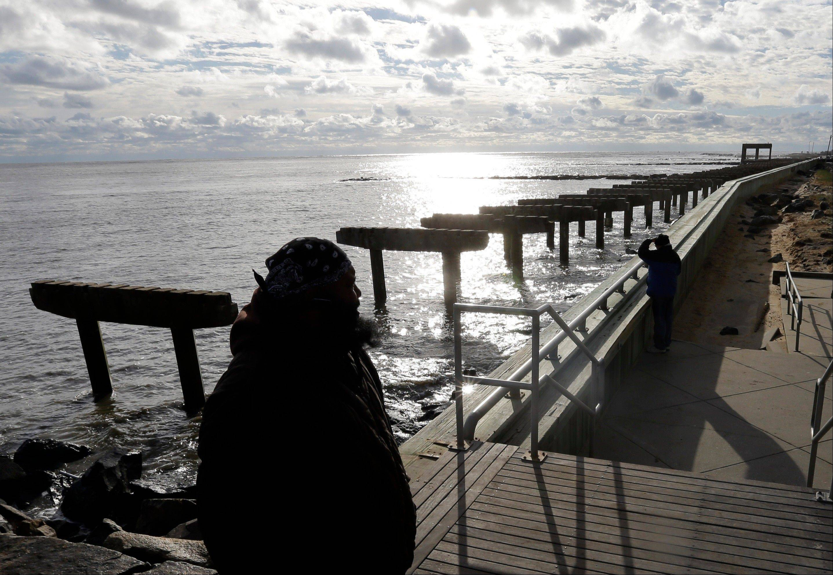 Lamar Stevens, bottom left, looks out at a boardwalk that was destroyed by superstorm Sandy in Atlantic City, N.J., Wednesday, Oct. 31, 2012.