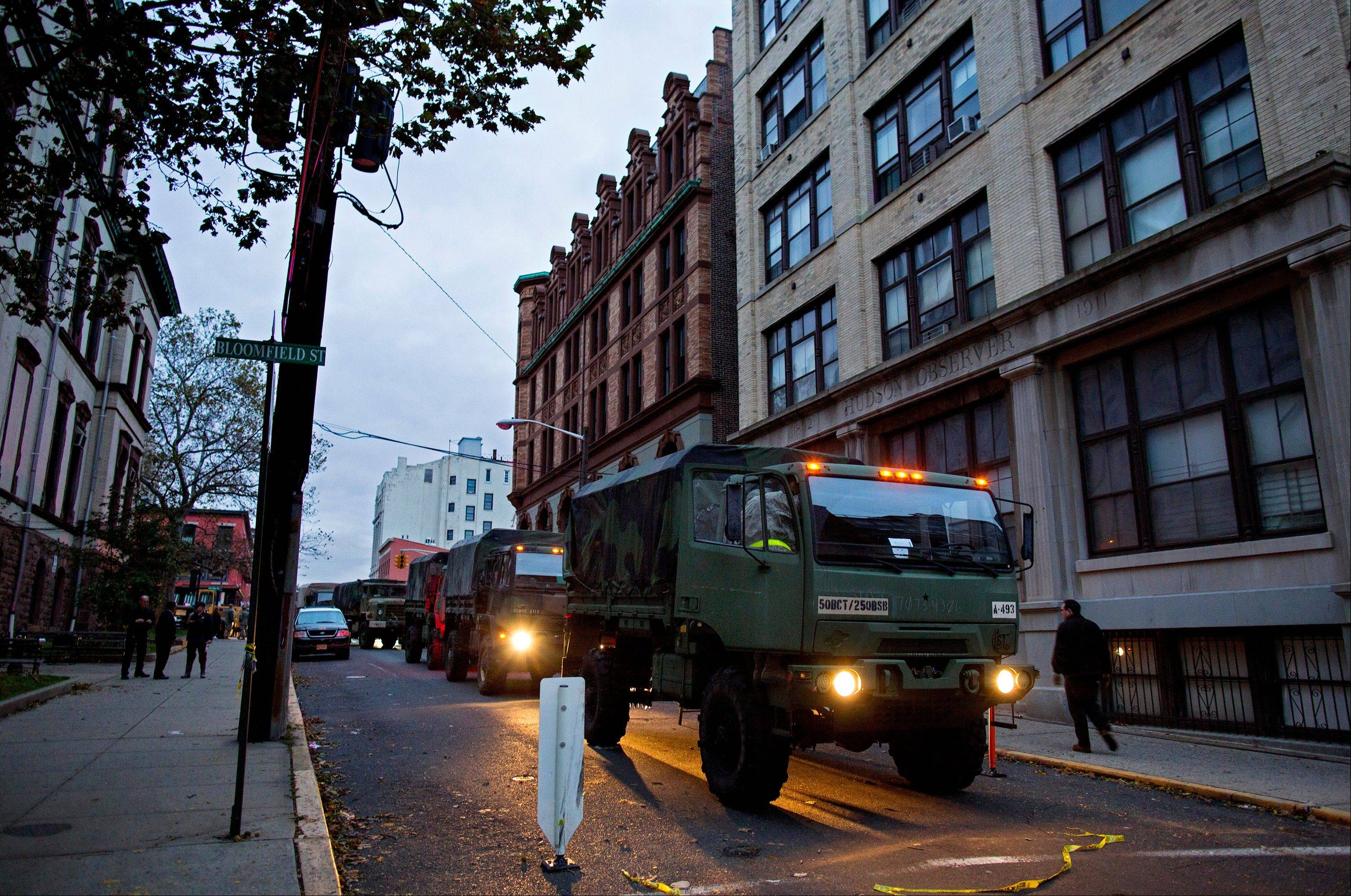 Members of the National Guard stand ready with large trucks used to pluck people from high water in Hoboken, N.J. Wednesday, Oct. 31, 2012 in the wake of superstorm Sandy. Parts of the city are still covered in standing water, trapping some residents in their homes.