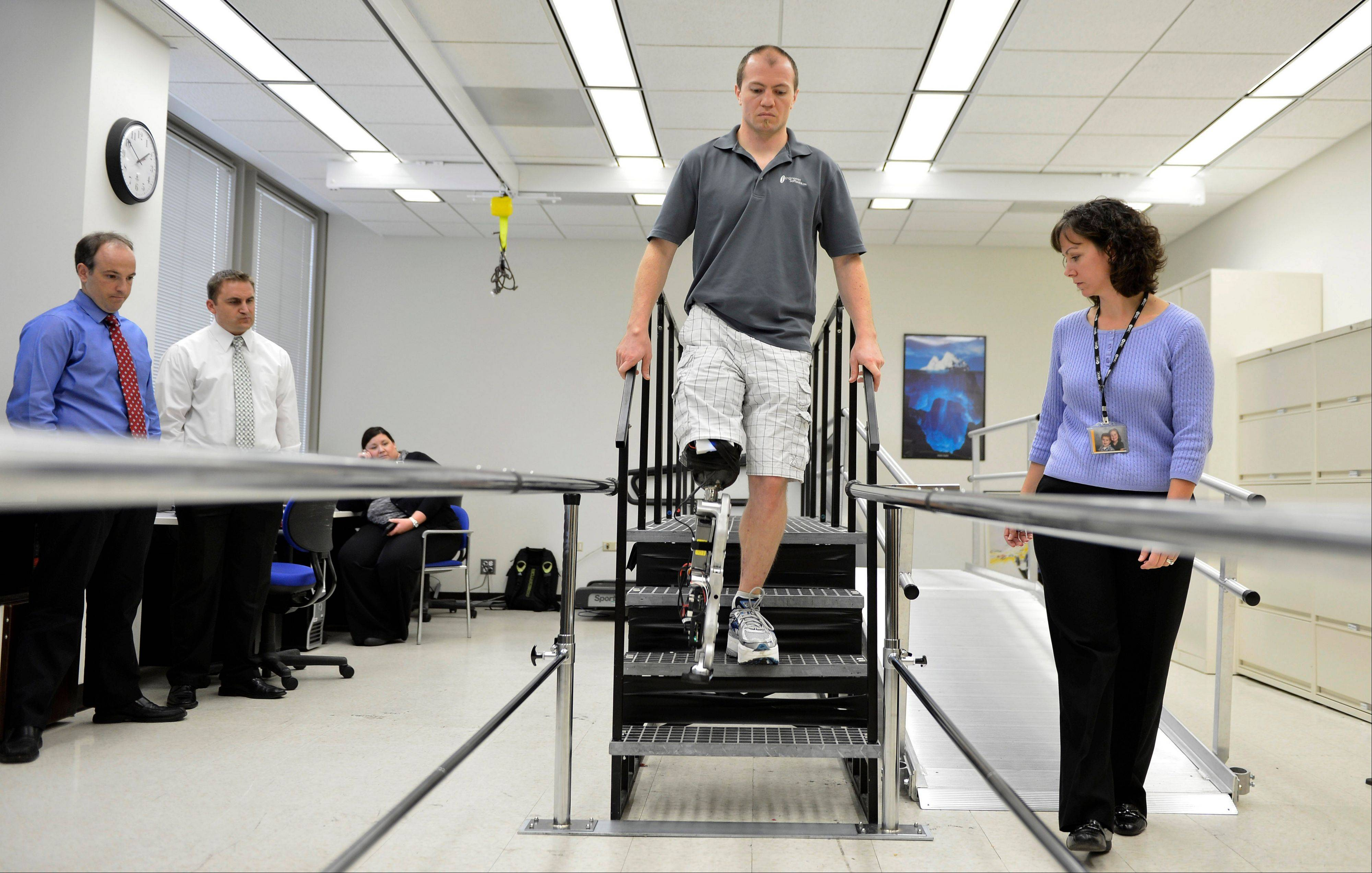"Physical therapist assistant Suzanne Finucane, right, helps Zac Vawter as he practices walking with an experimental ""bionic"" leg at the Rehabilitation Institute of Chicago."