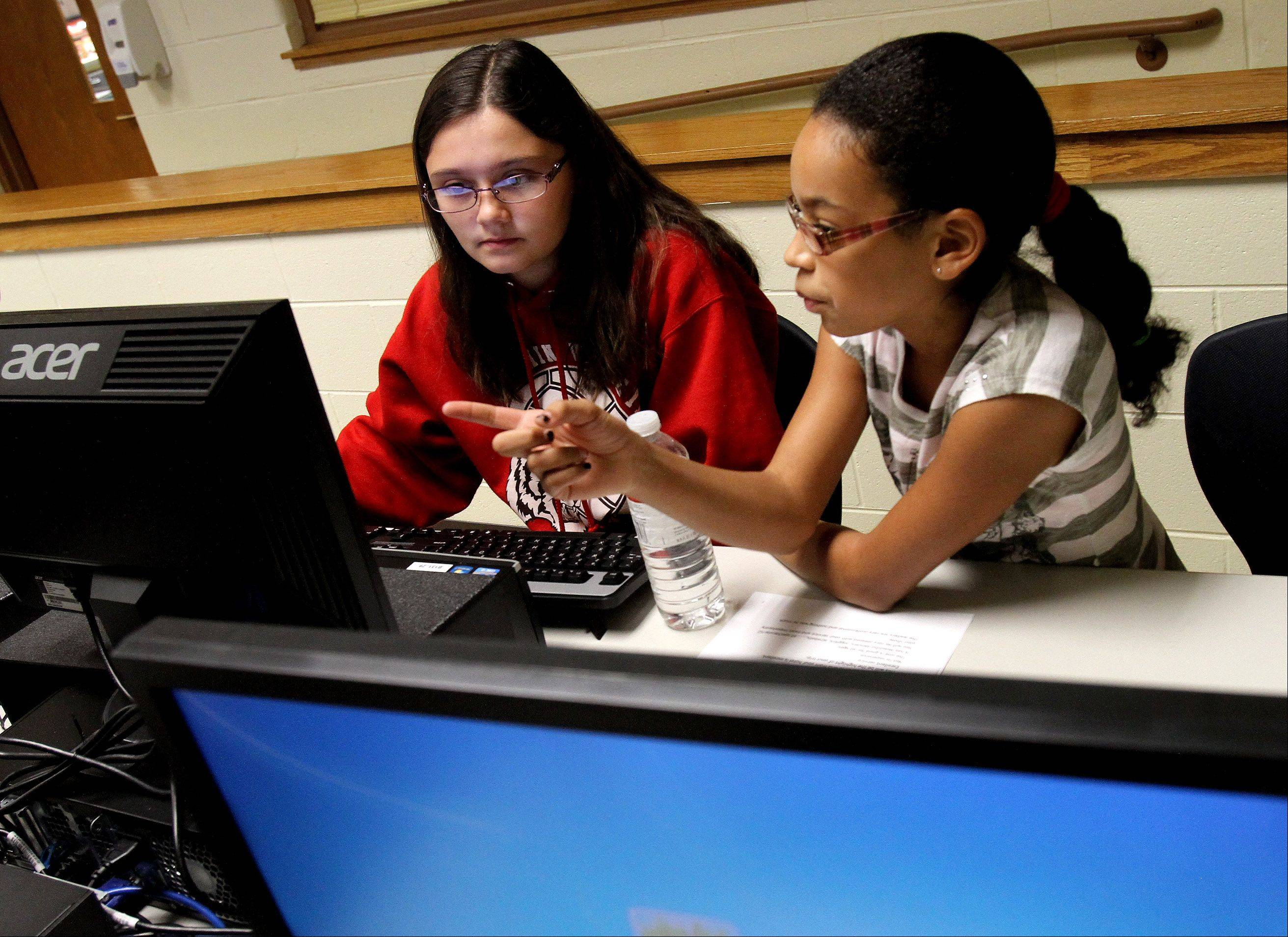 Christina Trigueros, left, and Kyra Hotdo, sixth-graders at Benjamin Middle School in West Chicago, work out a problem in computer applications class.