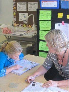 A fifth-grade student at Fearn Elementary School works with her teacher, Carol Laskowski, on reading.