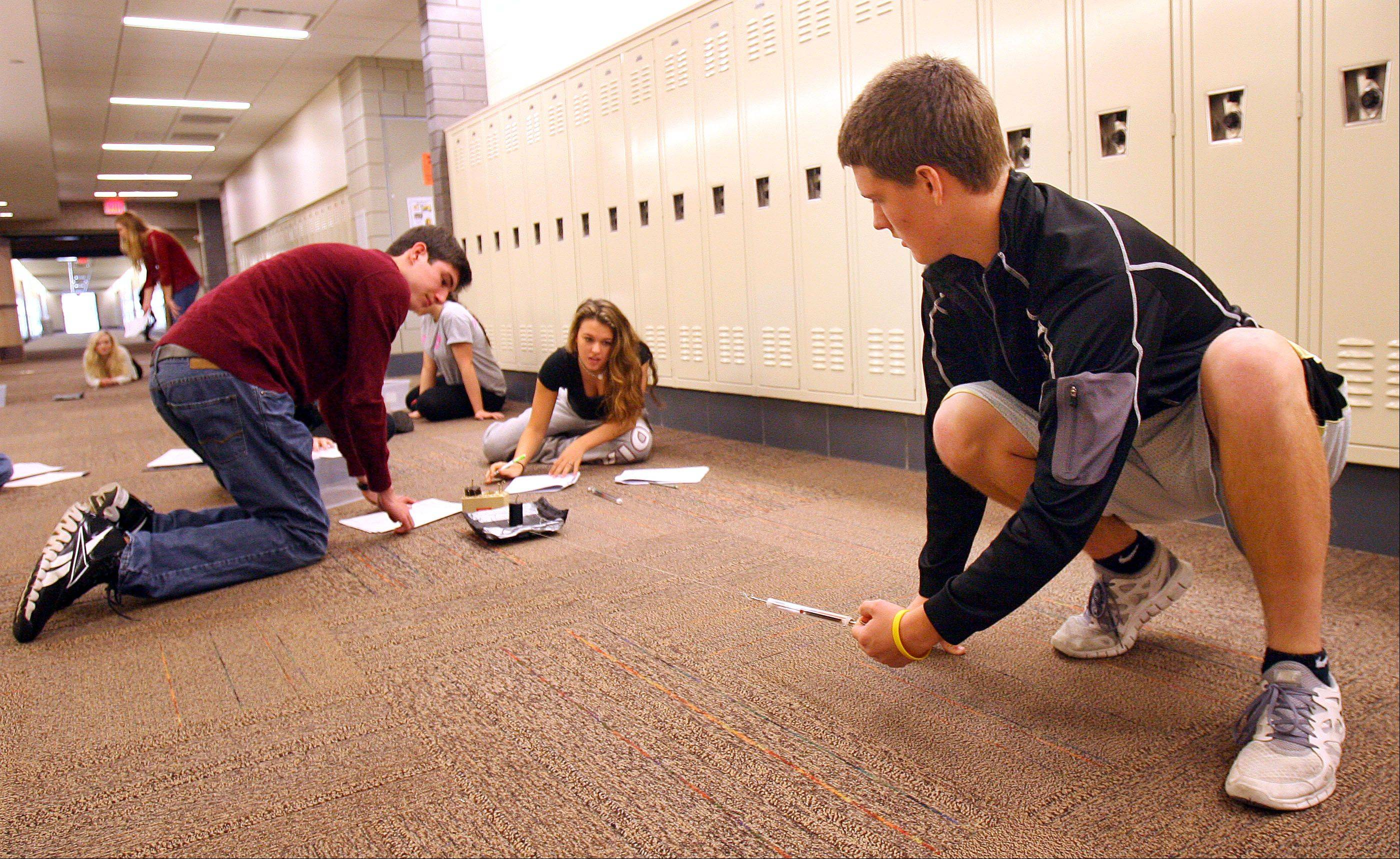 Accelerated physics students Connor Perlin of Kildeer, left, Hayley Wineberg of Buffalo Grove and Joey Traynor of Long Grove conduct an experiment in the hallway at Stevenson High School in Lincolnshire. Stevenson again swept the five academic categories on the annual state report card among 92 suburban high school districts examined by the Daily Herald.