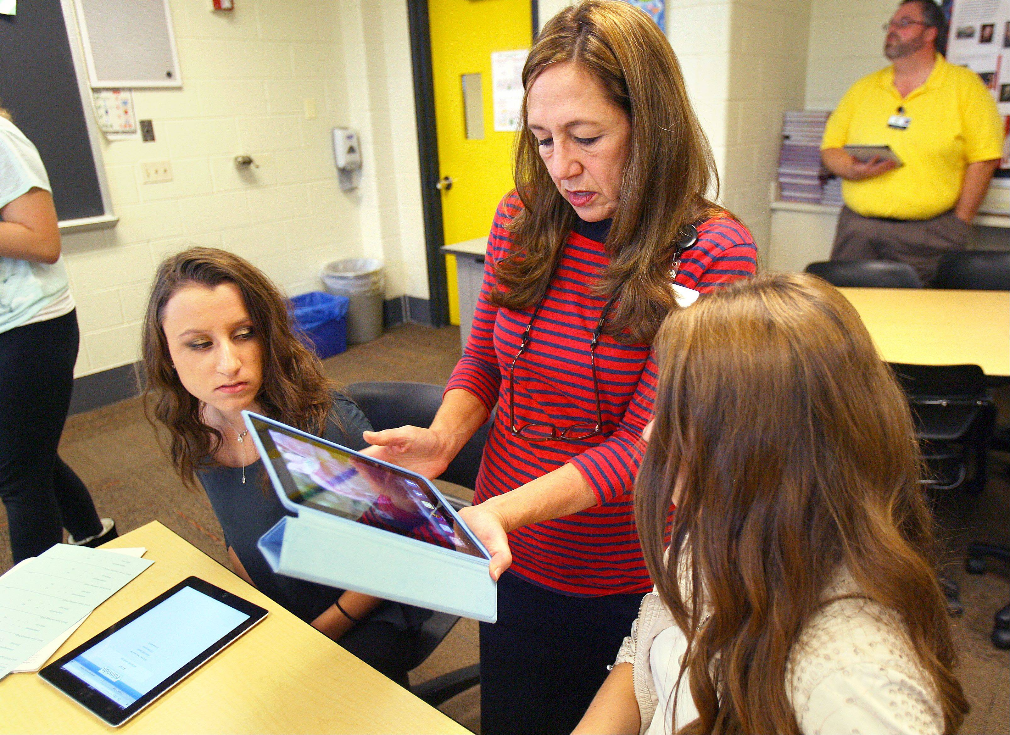 Spanish 2 teacher Lori Polin-Silva, middle, helps students Jessica Ascher, left, and Isabella Milejczyk with their iPads during class at Stevenson High School in Lincolnshire.