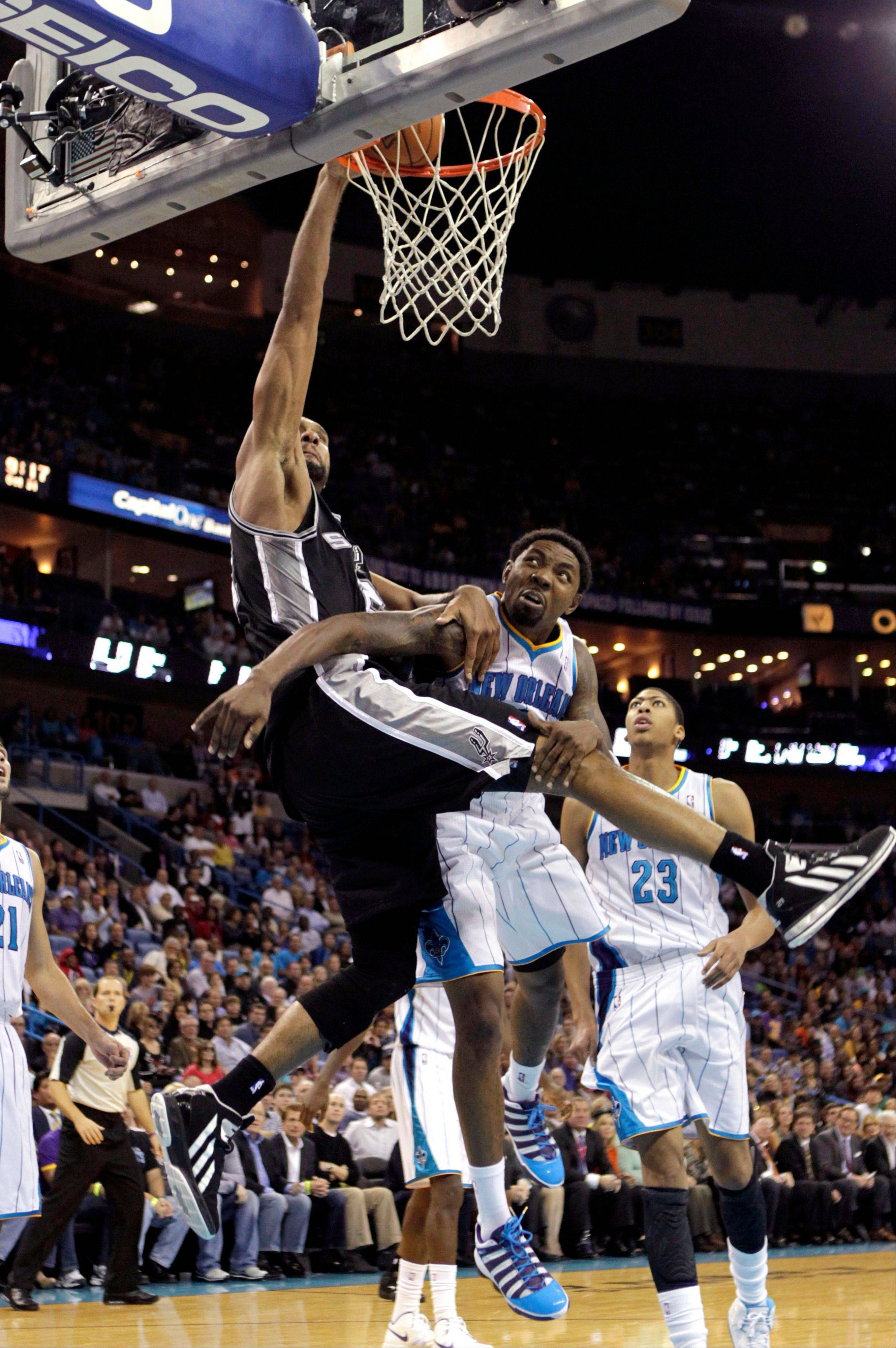 San Antonio Spurs power forward Tim Duncan goes to the basket against New Orleans Hornets shooting guard Roger Mason Jr., right, Wednesday during the second half in New Orleans. The Spurs won 95-99.
