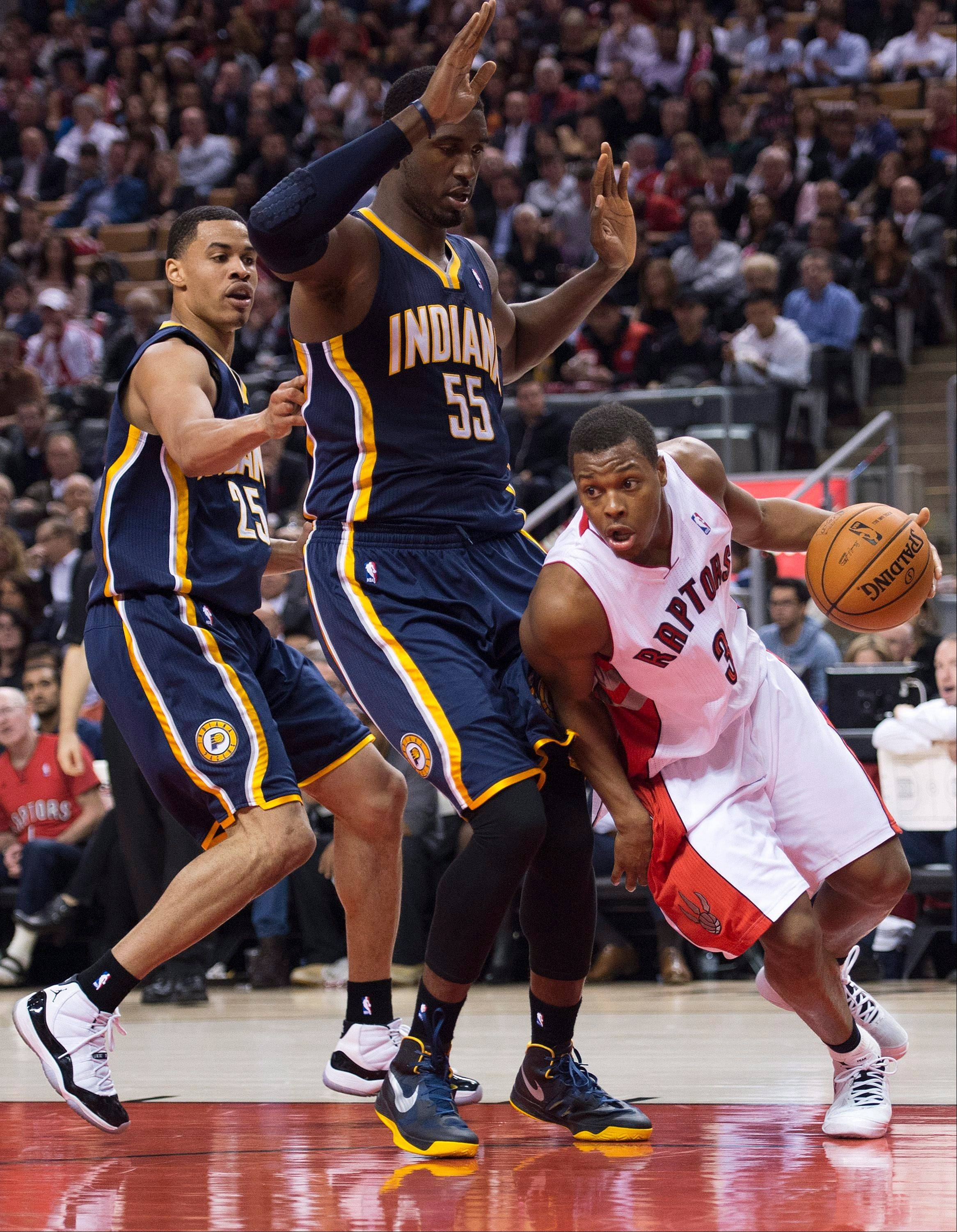 Toronto Raptors guard Kyle Lowry, right, drives to the net past Indiana Pacers forward Roy Hibbert, center, and Pacers guard Gerald Green, left, Wednesday during first half in Toronto.