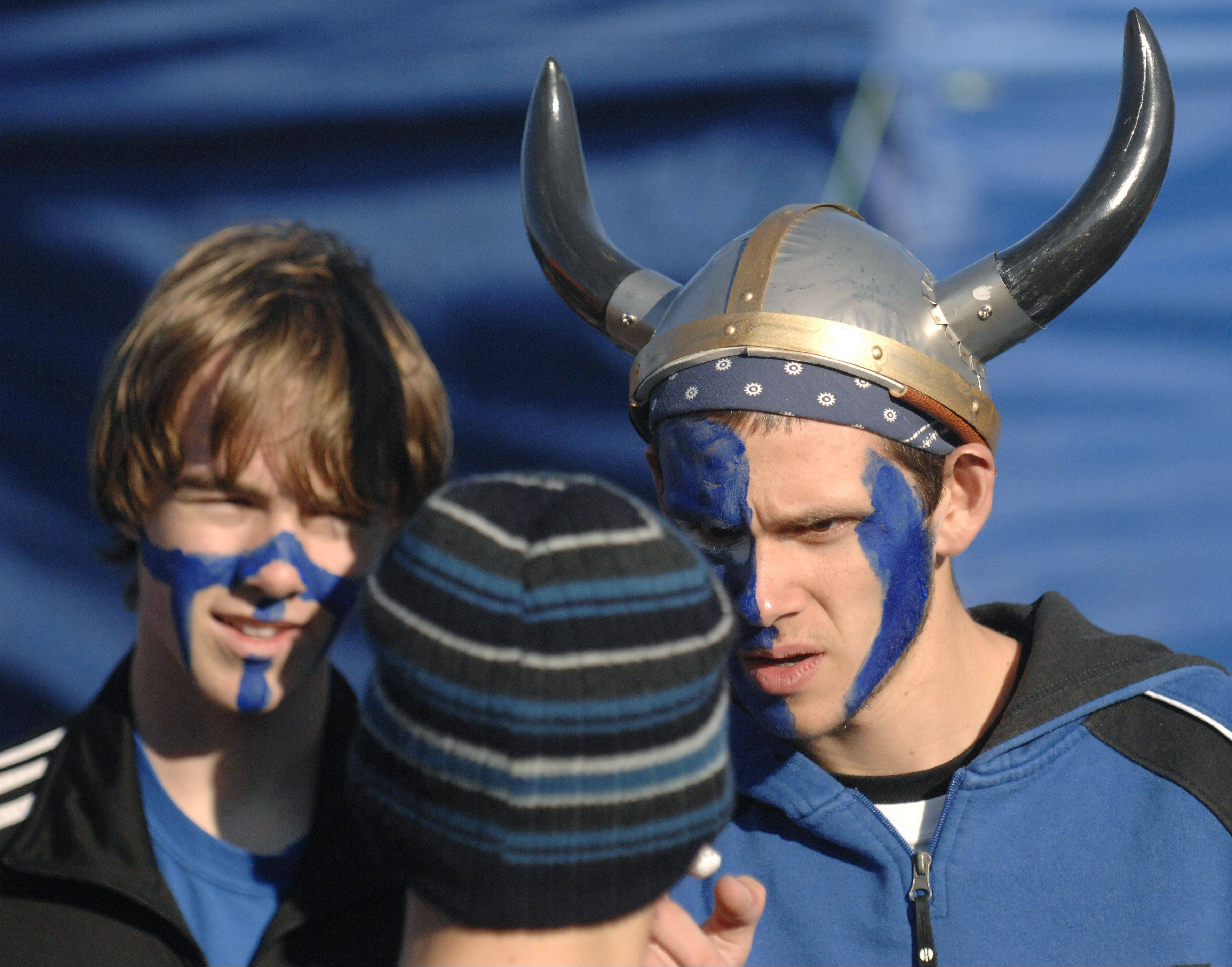 Laura Stoecker/lstoecker@dailyherald.comWearing a viking helmet, Mason Fisher applies face paint to Evan Miles before the start of the St. Charles East cross country sectional at LeRoy Oakes in St. Charles on Saturday, October 27.