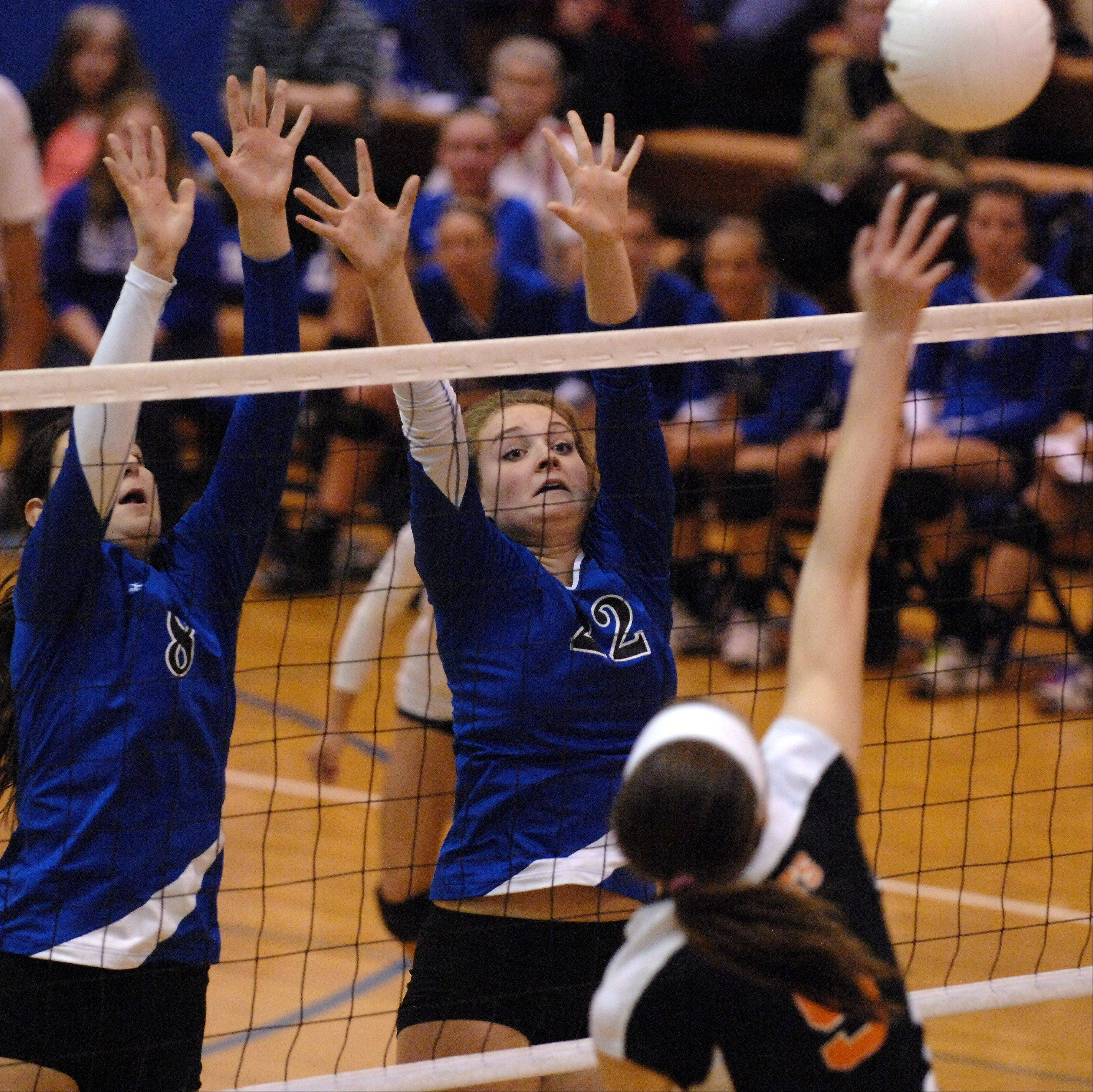 Rick West/rwest@dailyherald.comGeneva's Jess Wicinski, left, and Maddie Courter go up for a block against St. Charles East during Tuesday's sectional semifinals at Larkin High School in Elgin.