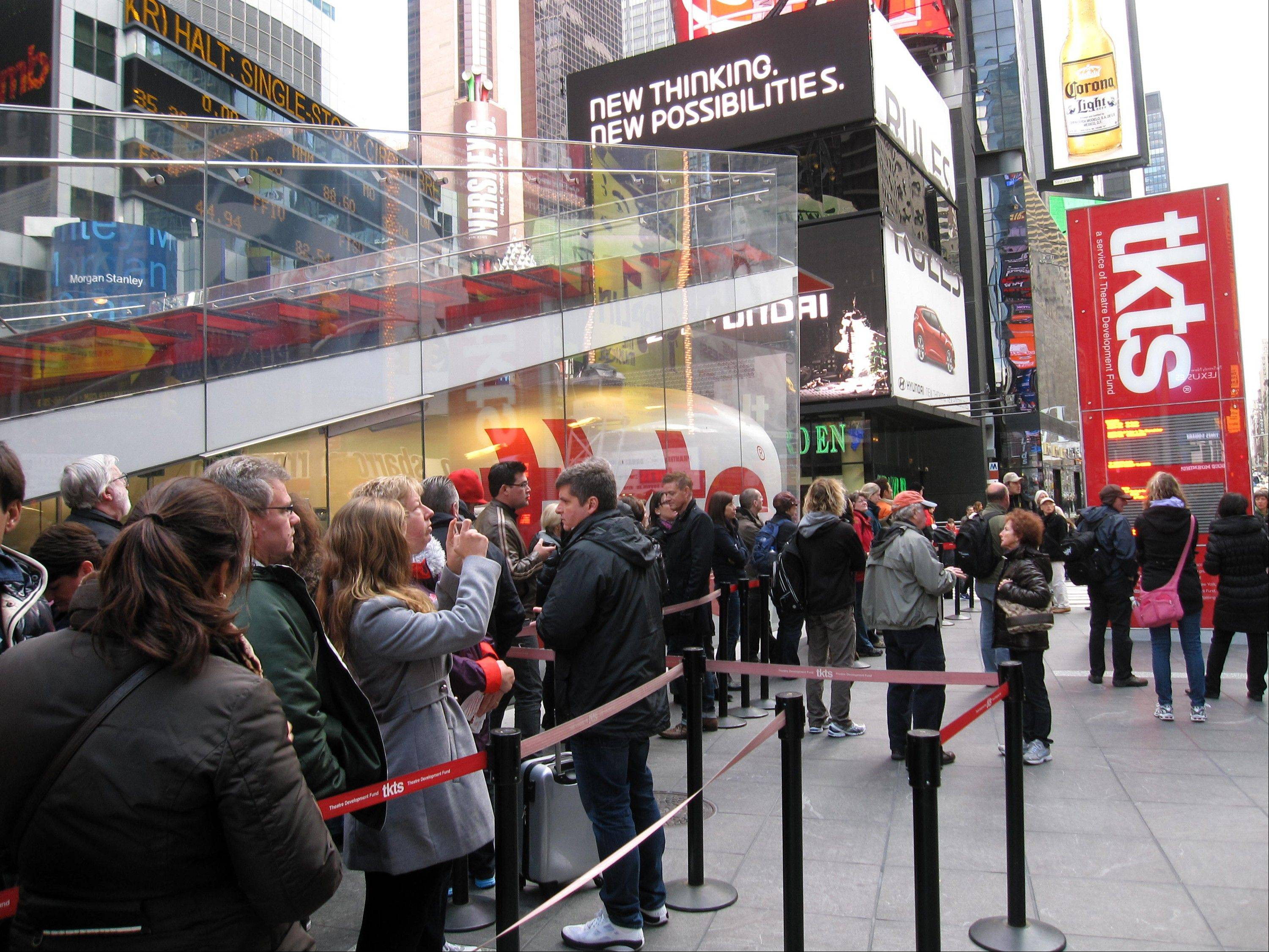 A line of ticket-buyers Wednesday wait at the TKTS booth, which sells discount tickets to Broadway shows in New York's Times Square. Most Broadway theaters reopened Wednesday for regular matinee and evening performances following several days of closures because of superstorm Sandy.
