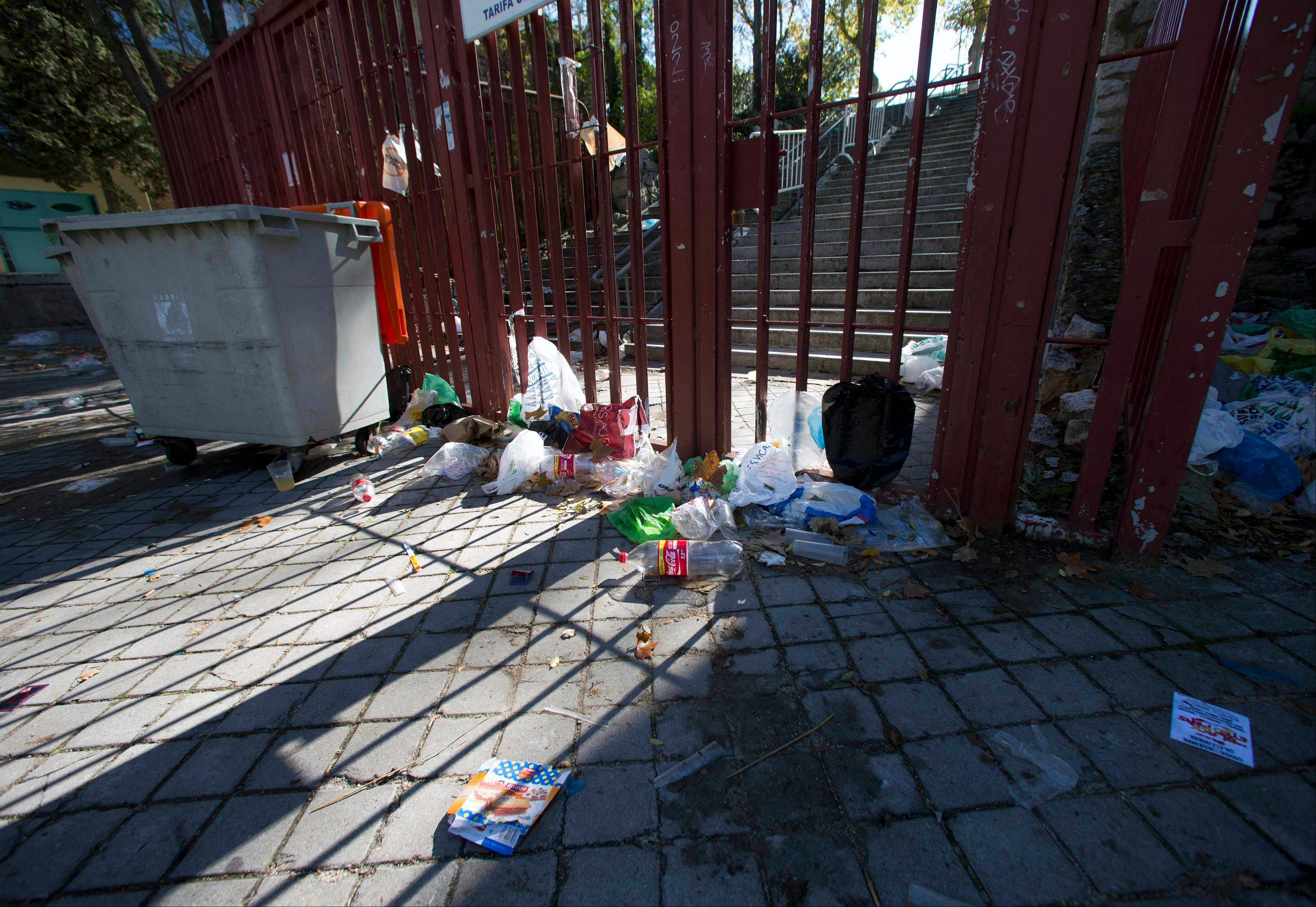 Empty bottles and other debris lie outside the closed gates of the Madrid Arena venue in Madrid, Thursday Nov. 1, 2012. Three women have been killed and two injured in a stampede during a large Halloween Night party at the venue.