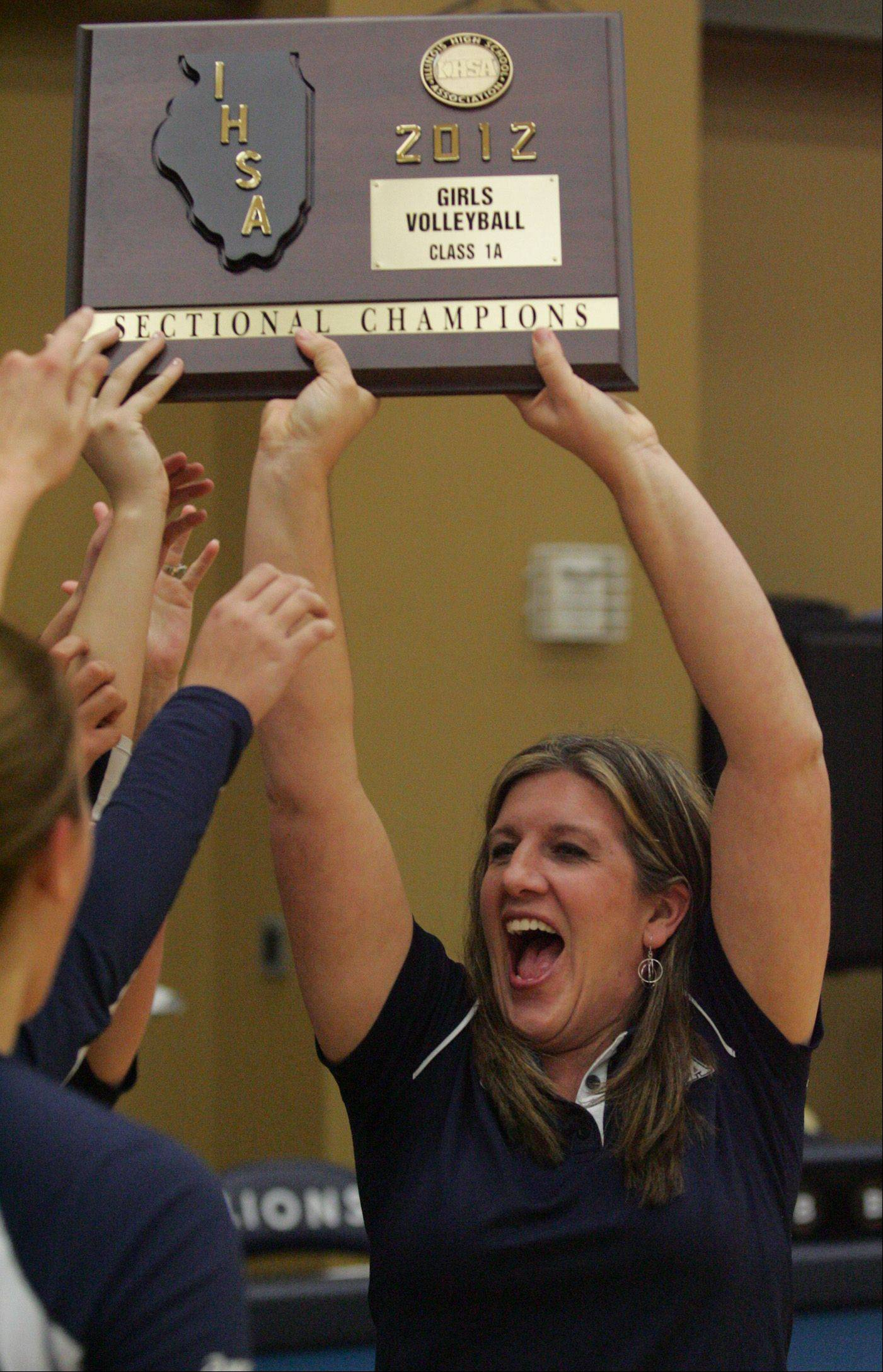 Harvest Christian coach Kim Floyd accepts the Class 1A sectional title trophy for her team after their win Thursday night over Morgan Park Academy.