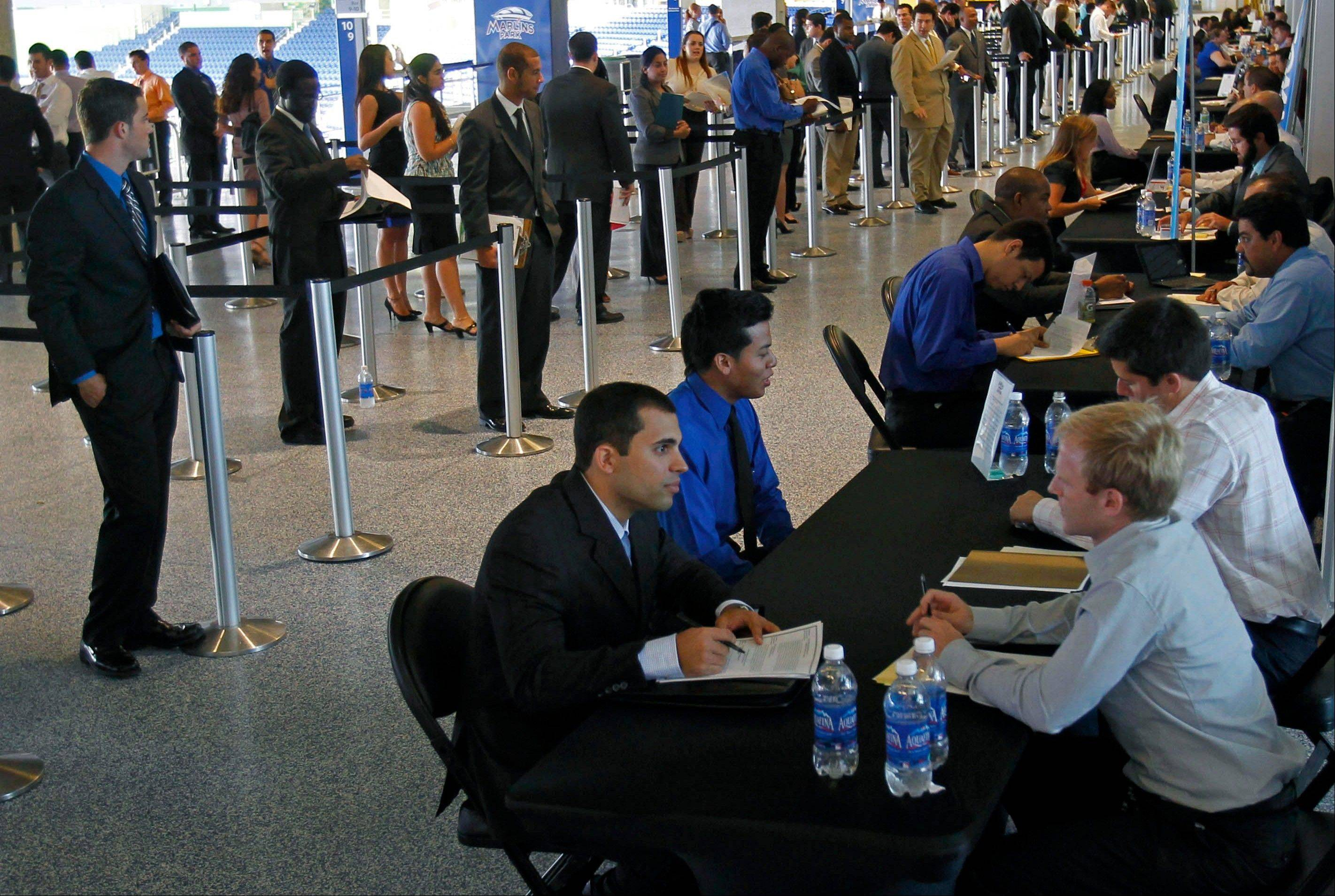 Job applicants are interviewed by Florida Marlins staff at Marlins Park in Miami. Weekly applications for U.S. unemployment aid fell last week to a seasonally adjusted 369,000, a level consistent with modest hiring.