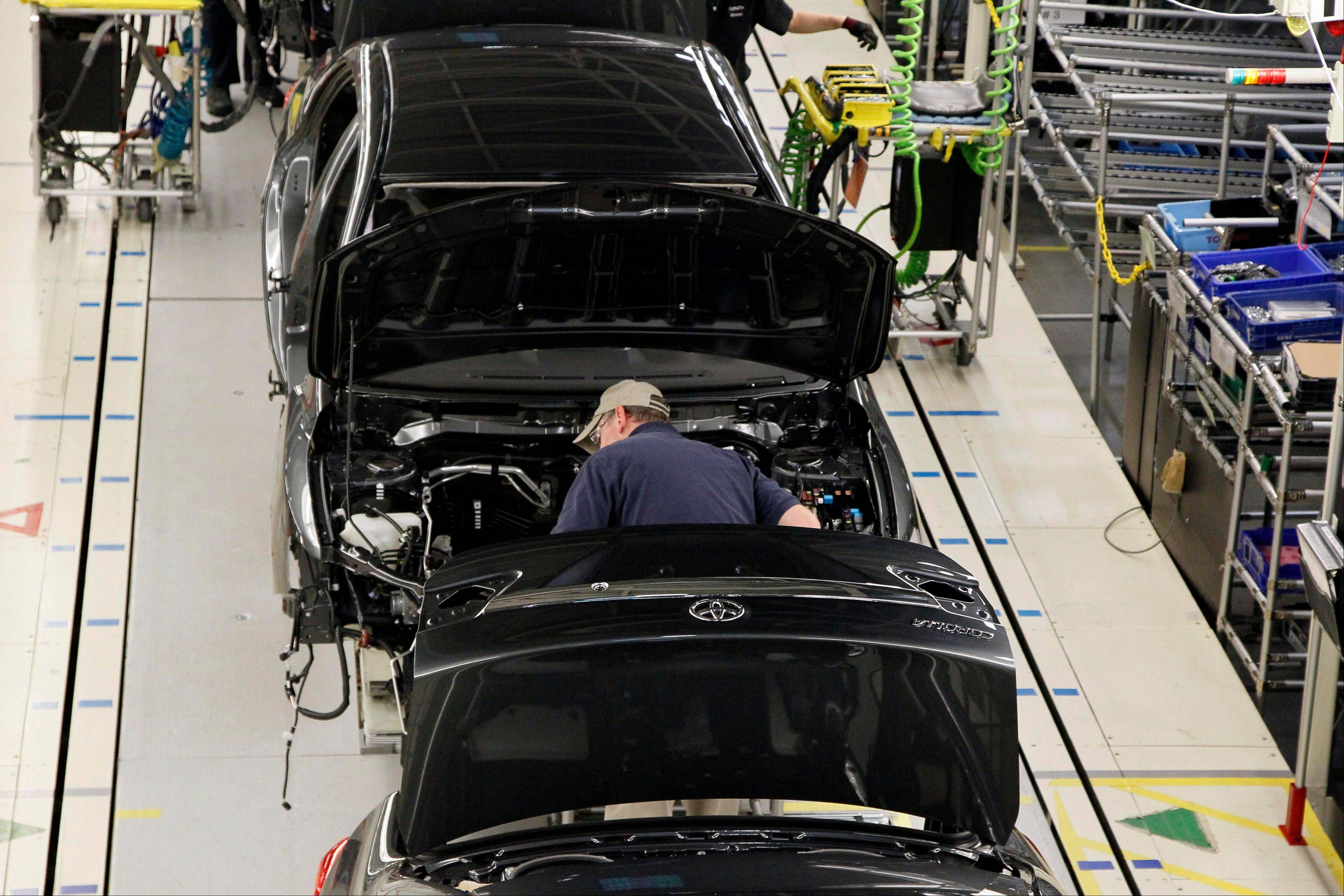 An employee works on the trim line as he checks the chassis of a Toyota Corolla as it rolls down assembly line at the Toyota Motor Manufacturing plant in Blue Springs, Miss.