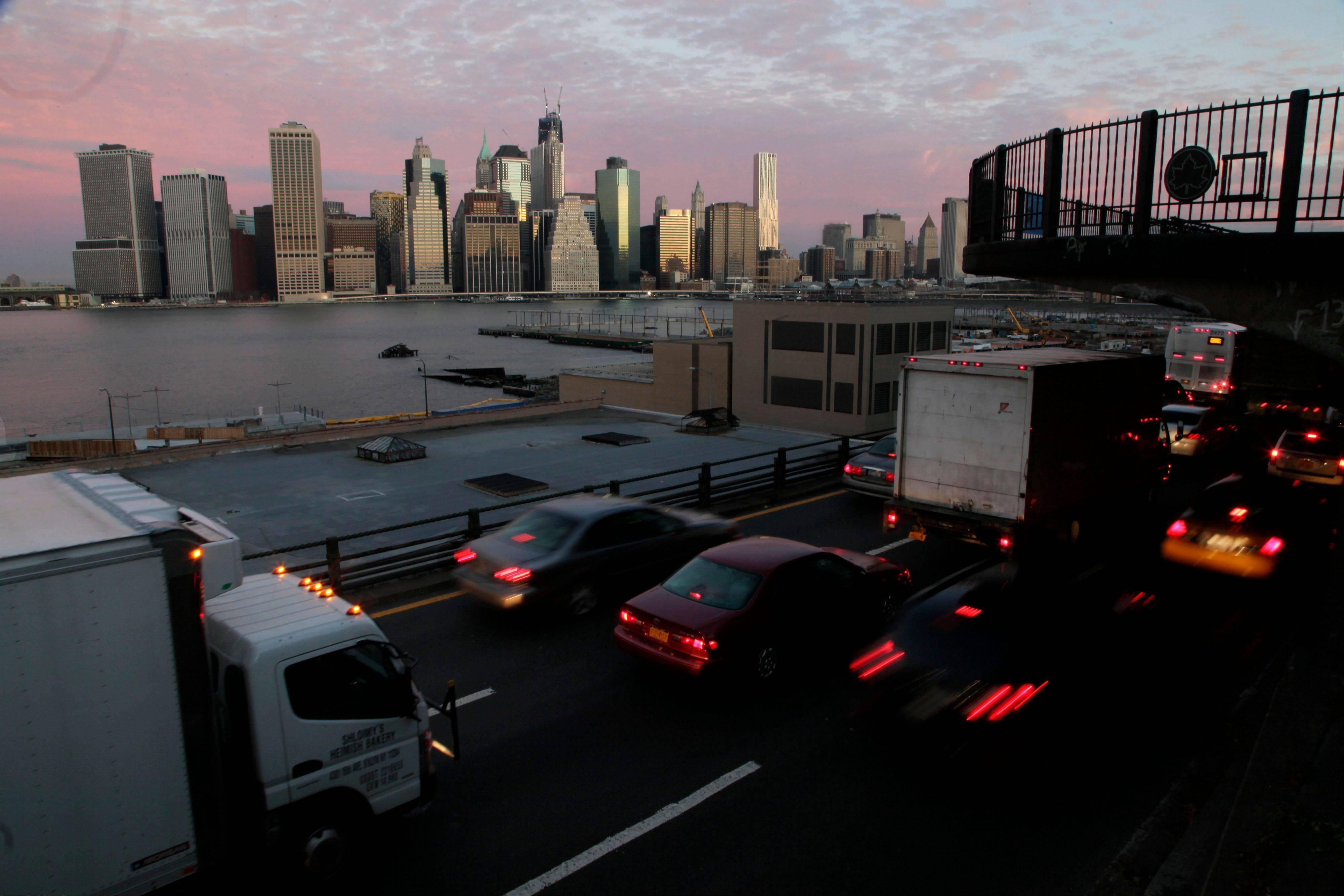 Early morning traffic in Brooklyn moves slowly beneath the Manhattan skyline, Thursday.