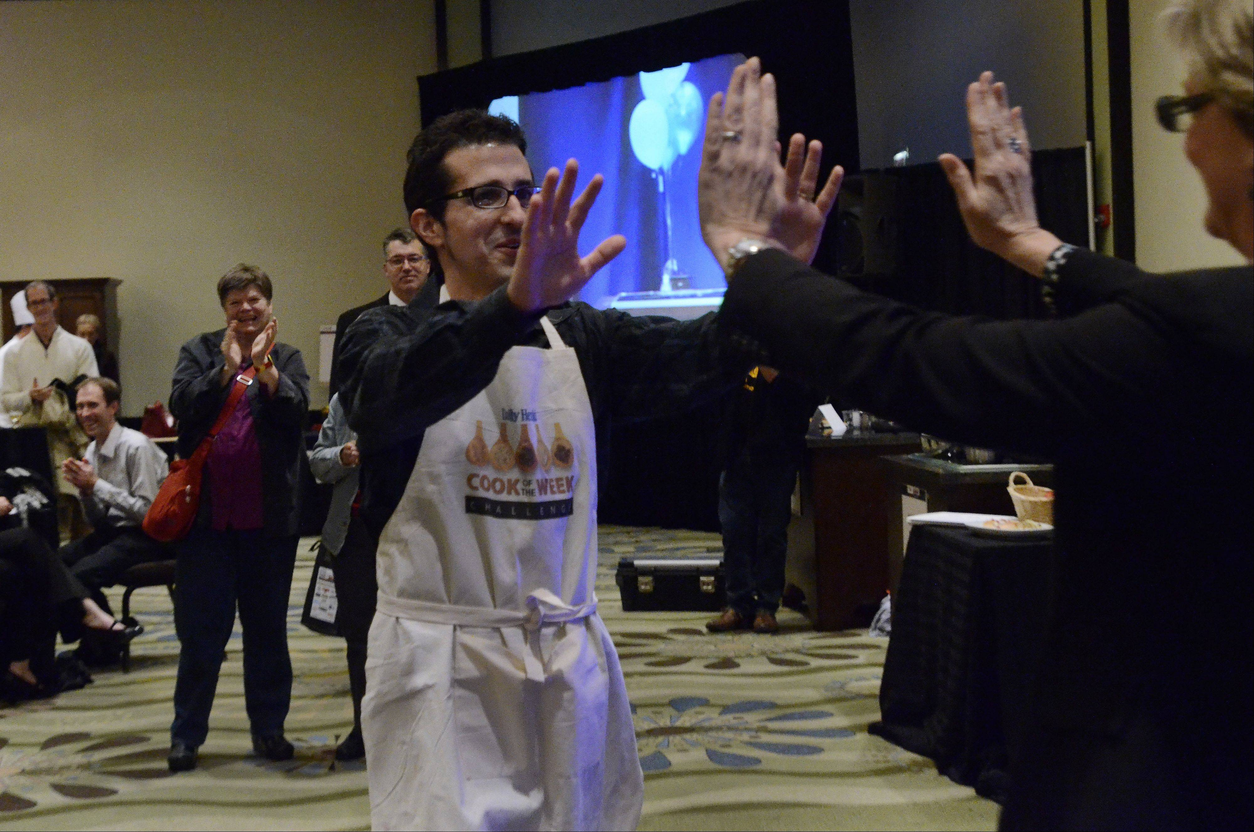 Michael Pennisi of Carpentersville is congratulated by Eileen Brown, Daily Herald Assistant Vice President/Director of Strategic Marketing and Innovation, after winning the Cook of the Week Challenge Cookoff.