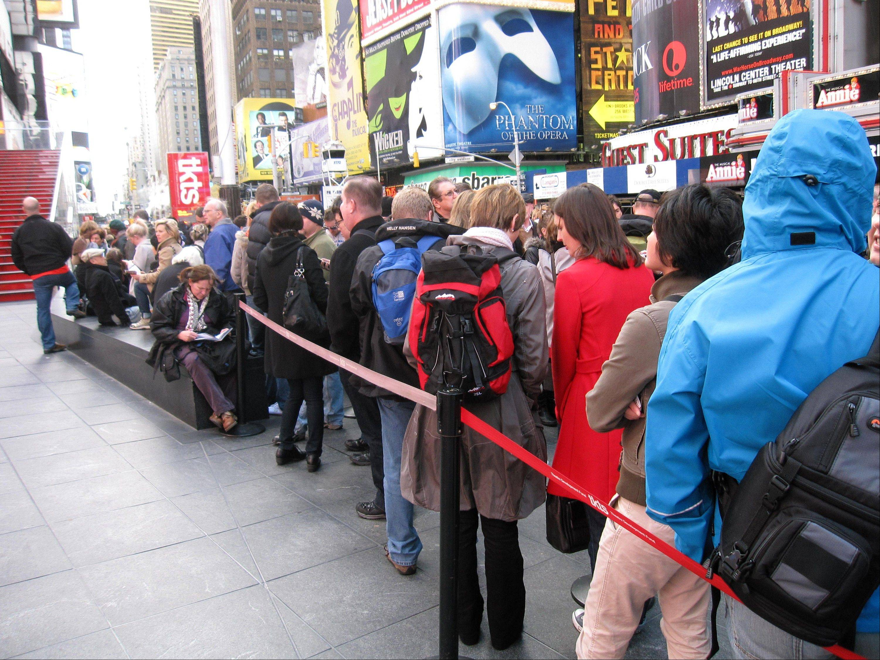 A line of ticket-buyers Wednesday wait at the TKTS booth in Times Square, which sells discount tickets to Broadway shows. Most Broadway theaters were reopening Wednesday following several days of closures related to superstorm Sandy.