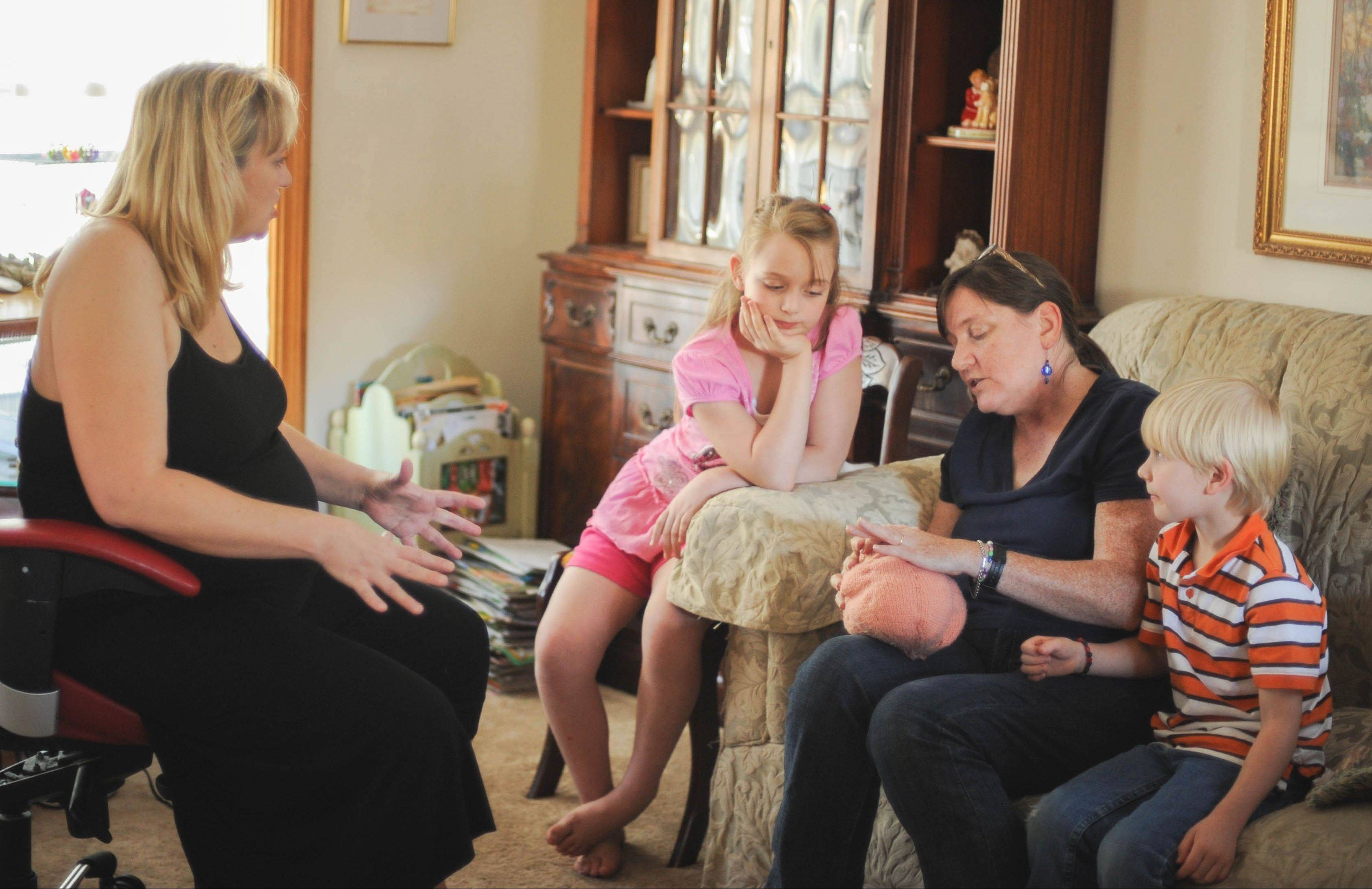 Allison Sass and doula Deb Lawrence explain to Charlotte Sass, 9, center, and Evan Sass, 6, right, what will happen when their brother, Paul, is born.
