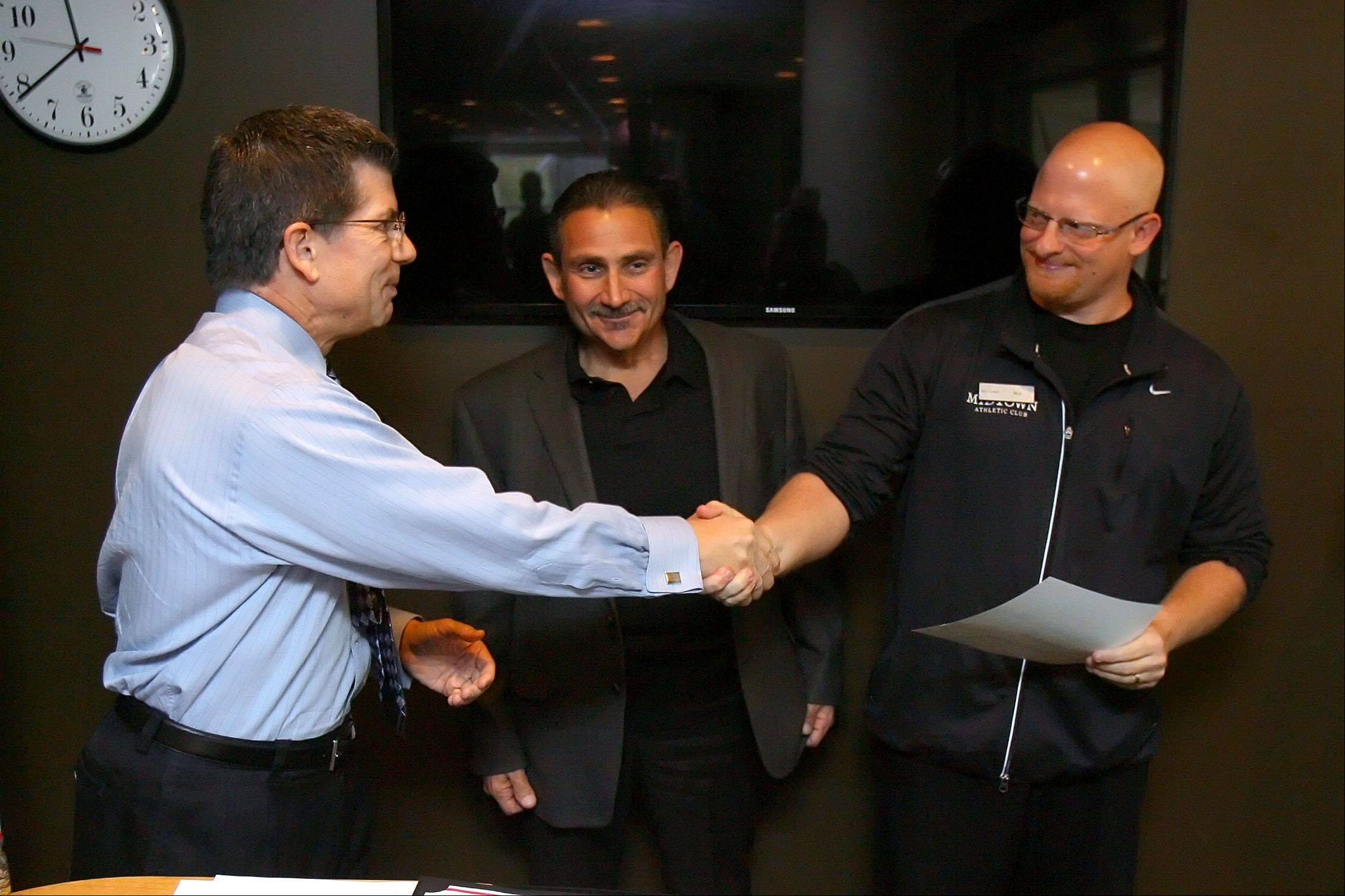Midtown Athletic Club personal trainer Rich Rossi, right, shakes hands with Midtown Athletic Club general manager Rich Novelli. Rossi was honored for saving Gary Greenberg of Highland Park, middle, after he suffered a heart attack at the facility two weeks ago.
