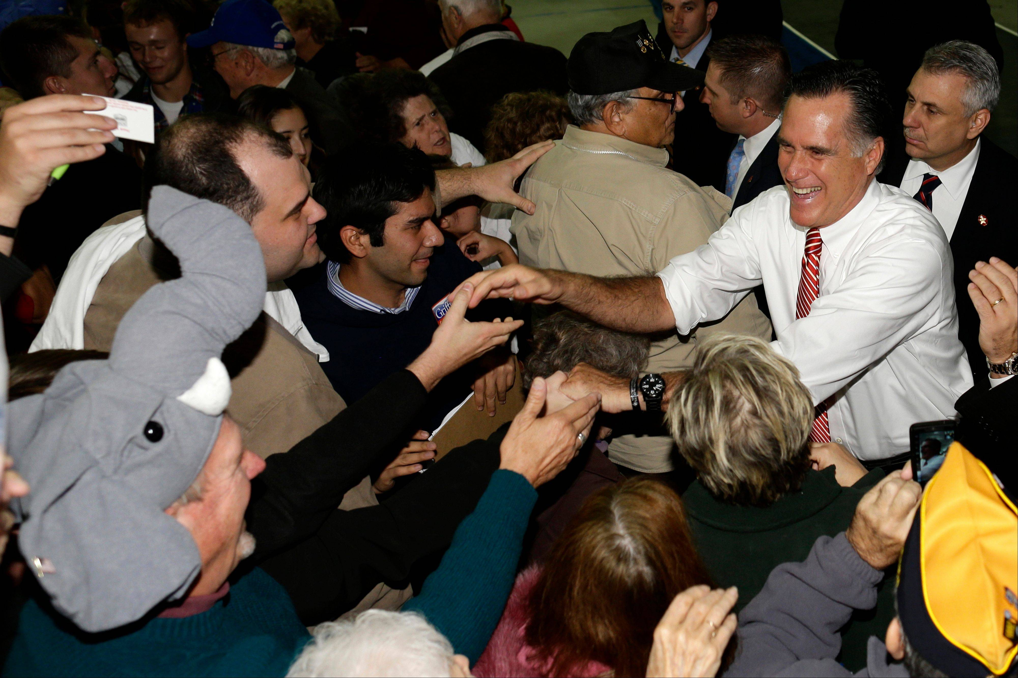 Republican presidential candidate, former Massachusetts Gov. Mitt Romney greets supporters, including one wearing an elephant hat, left, as he campaigns at Integrity Windows in Roanoke, Va., Thursday, Nov. 1, 2012.