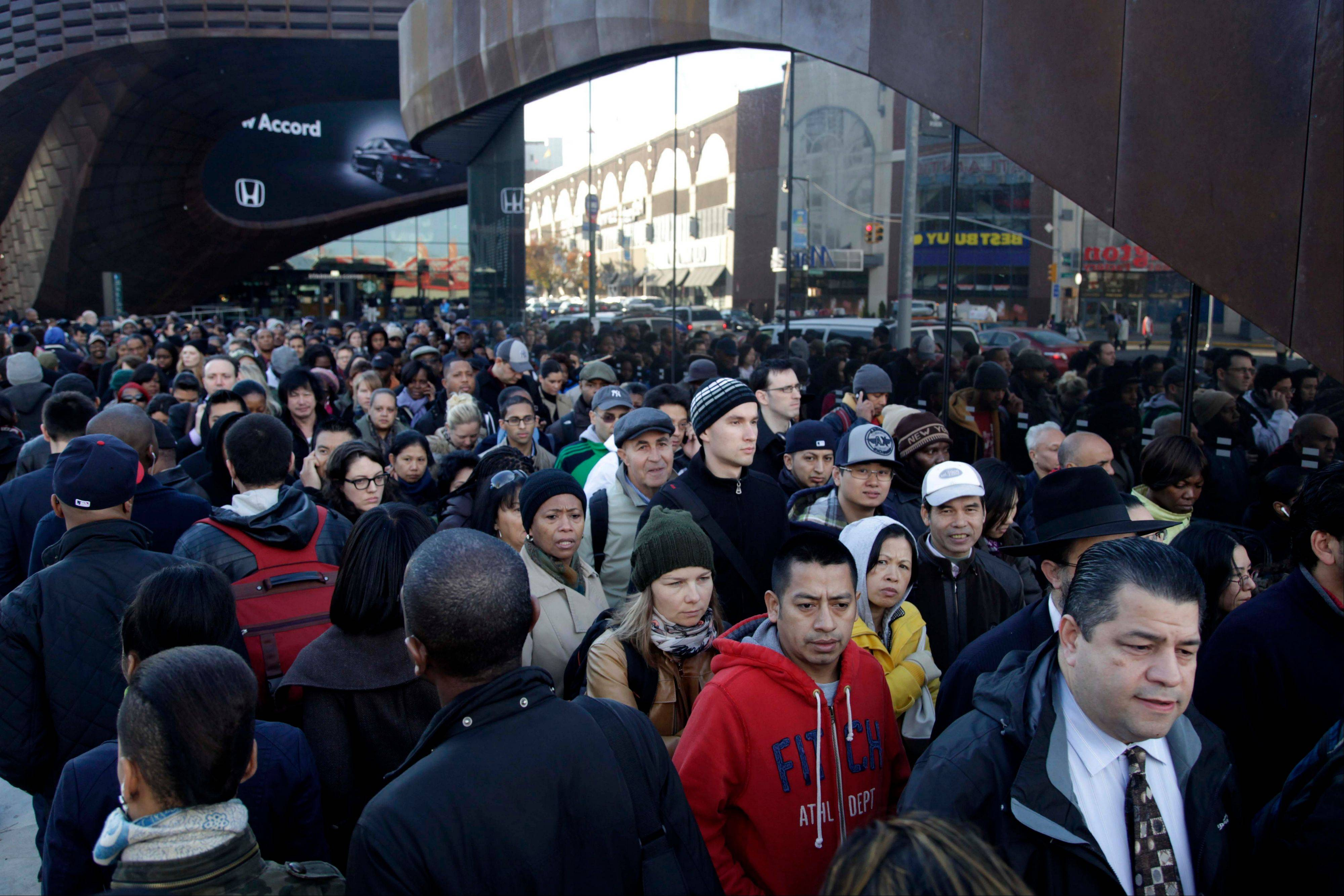 Commuters wait in a line to board buses into Manhattan in front of the Barclays Center in Brooklyn, New York, Thursday. The line stretched twice around the arena and commuters reported wait times of one to three hours to get on a bus.