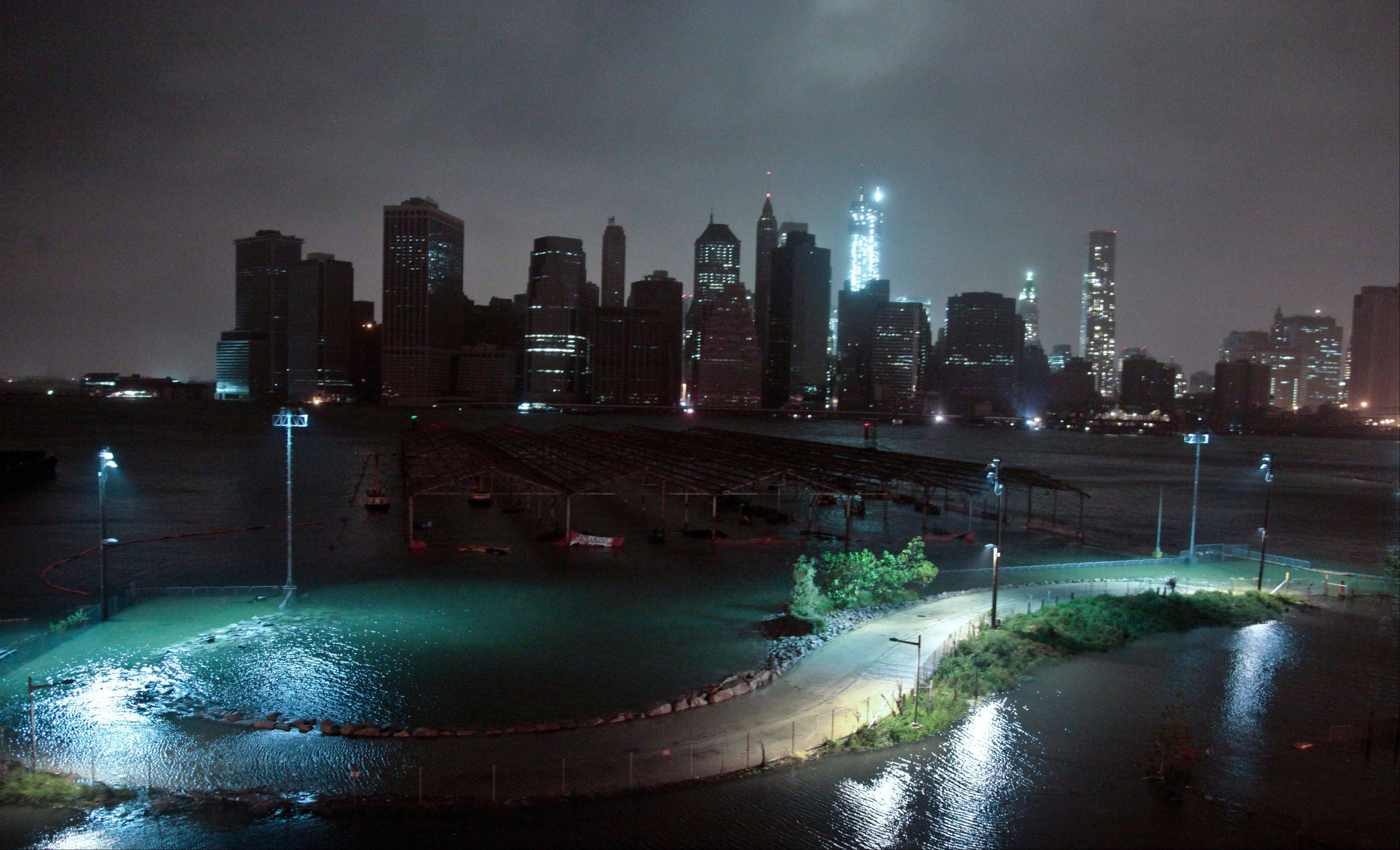 Lower Manhattan went dark on Monday after Hurricane Sandy forced the shutdown of mass transit, schools and financial markets and left millions without electricity.