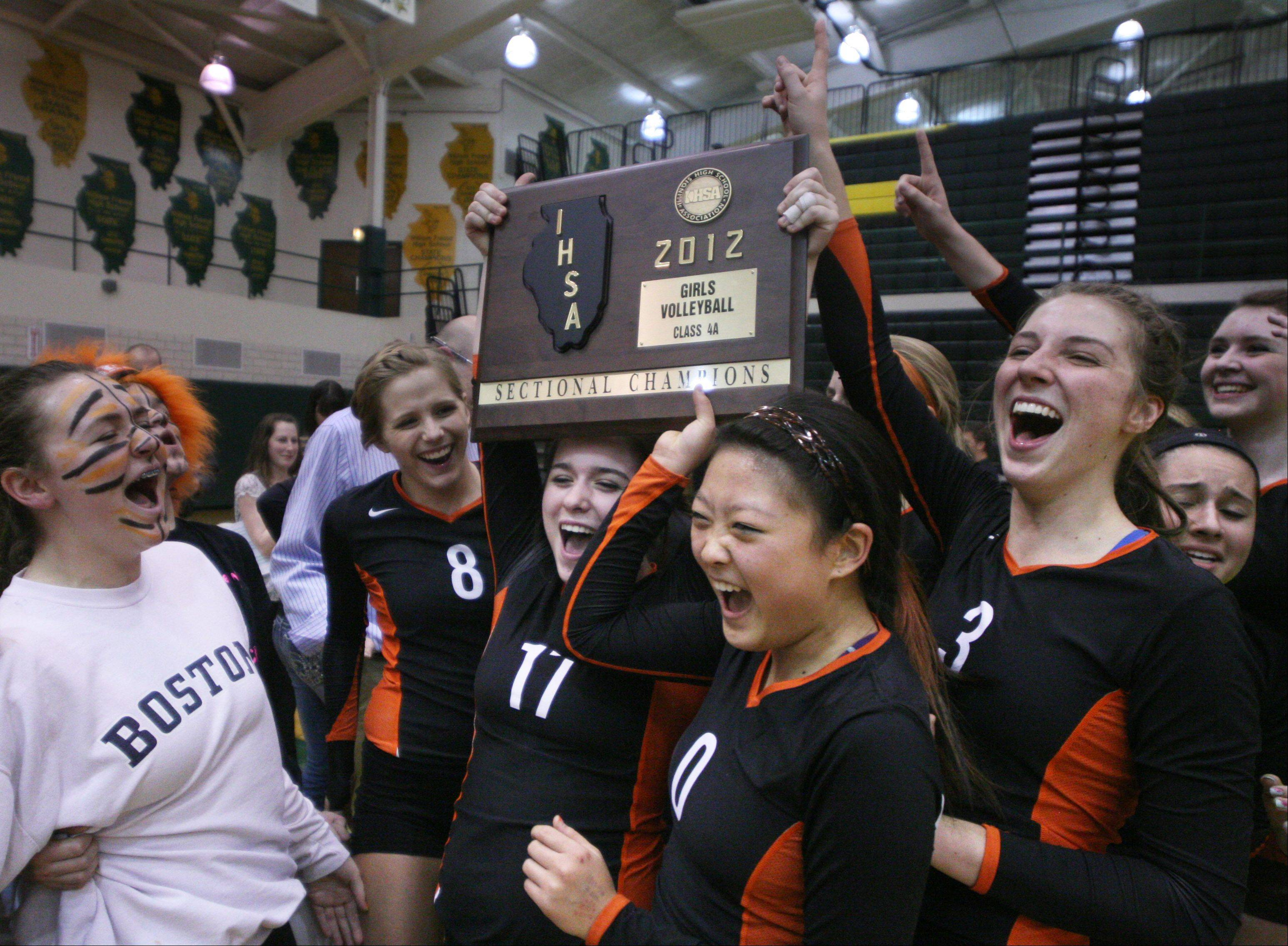 Libertyville players celebrate with their trophy after winning a sectional title at Fremd on Thursday night.