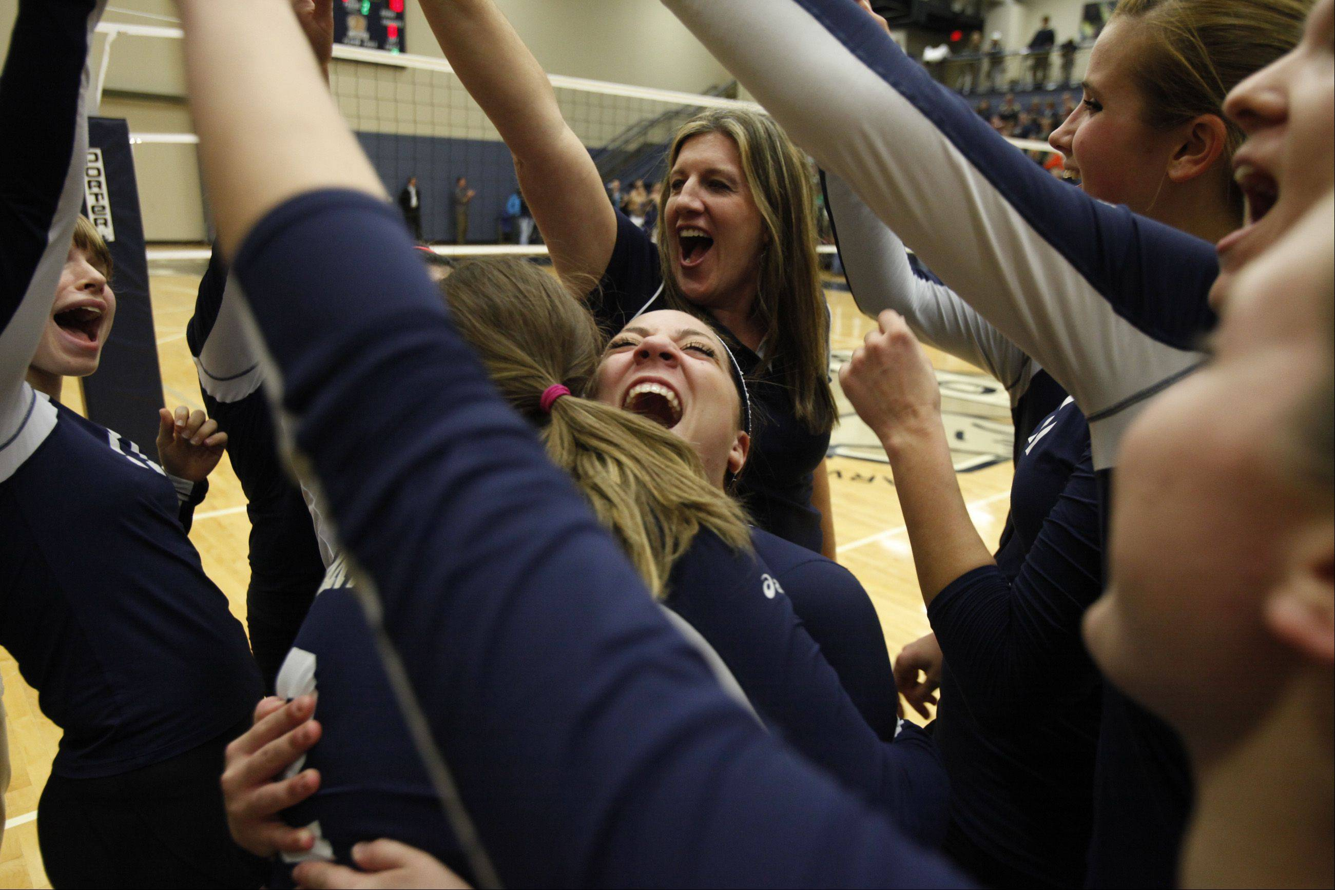 Harvest Christian players celebrate around teammate Shayna Manusos after winning the sectional title Thursday night in Elgin.