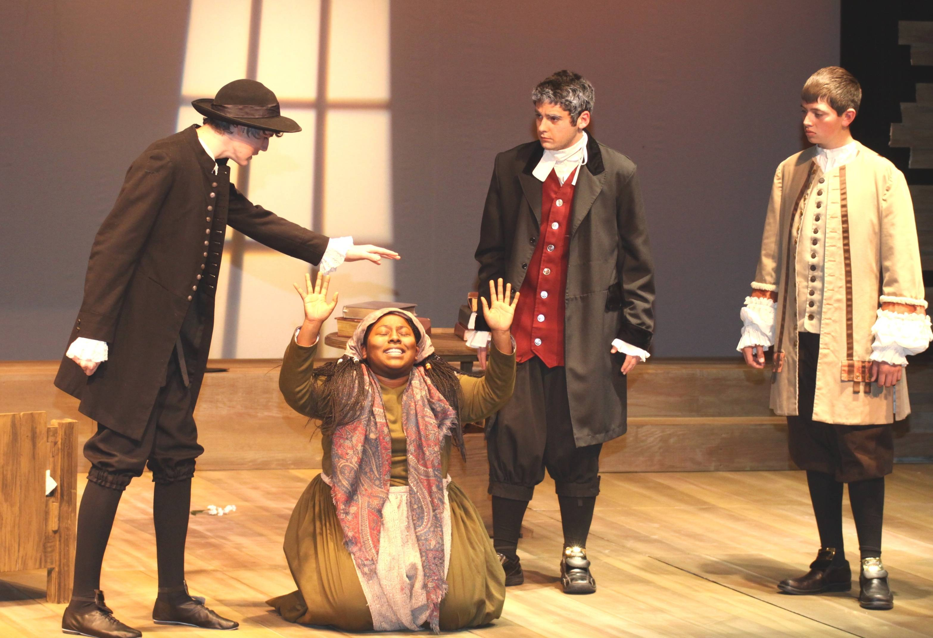 Reverend Hale(played by sophomore  Lucas Bennett) interrogates Tituba (played by senior Alyssa Kindell) as Reverend Parris (played by junior John Tasch) and Thomas Putnam (played by freshman Nick Martin) look on.