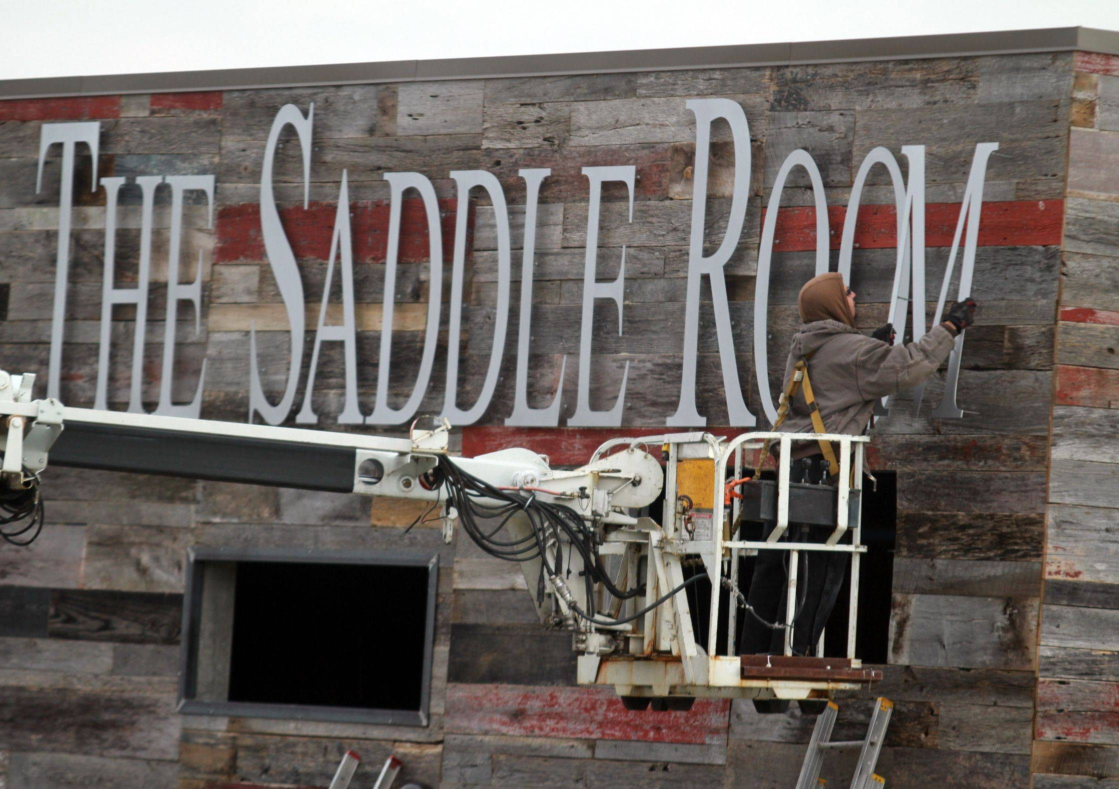"The letter ""M"" is hung on the exterior of The Saddle Room, an off-track betting parlor and restaurant in Hoffman Estates that opens today."
