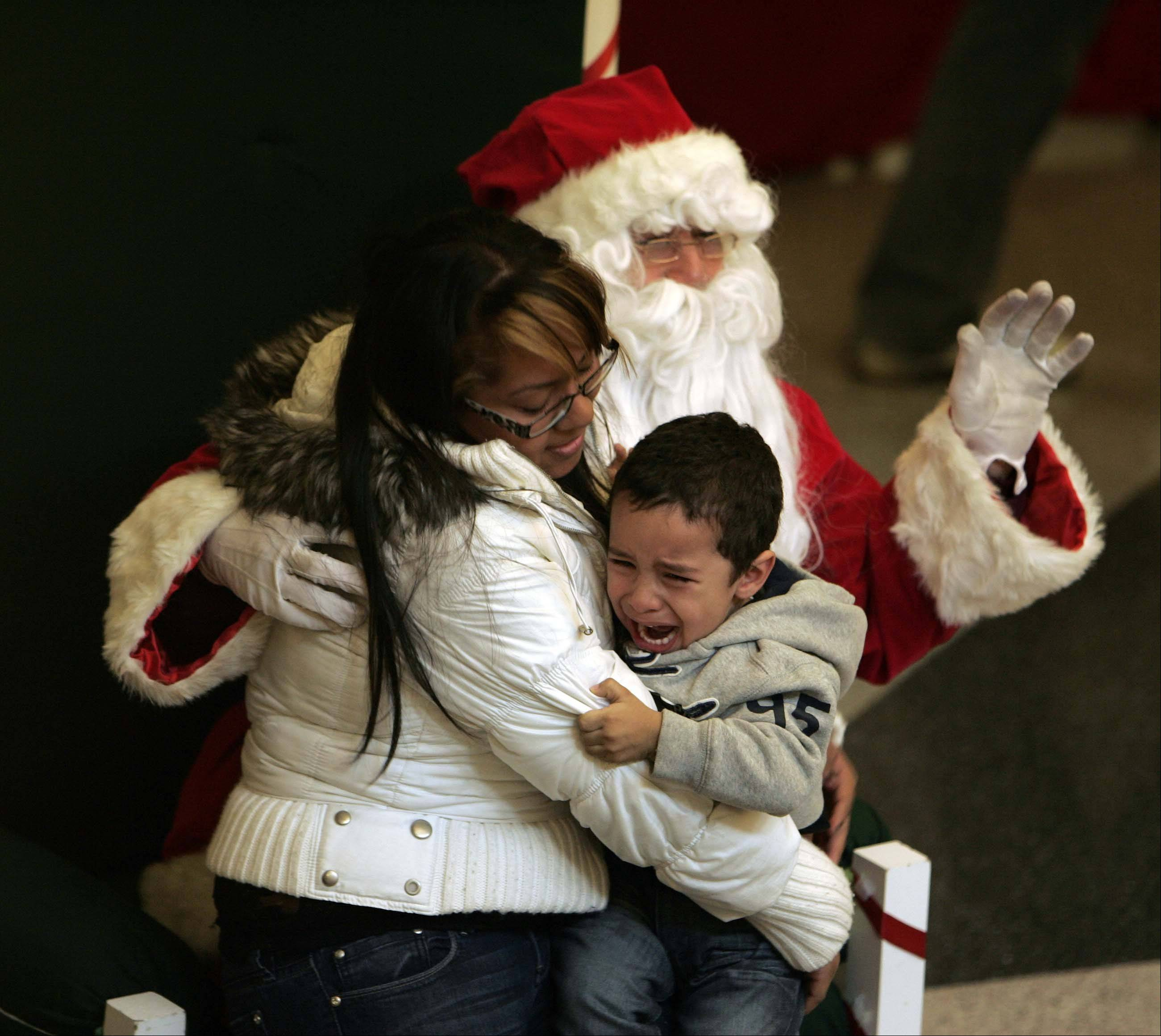 Brian Hill/bhill@dailyherald.com Sonia Albarran of Elgin tries to comfort her son Xavier Marques, 2, while visiting Santa during the Elgin Home for the Holidays, event Saturday at the Gail Borden Public Library in Elgin.