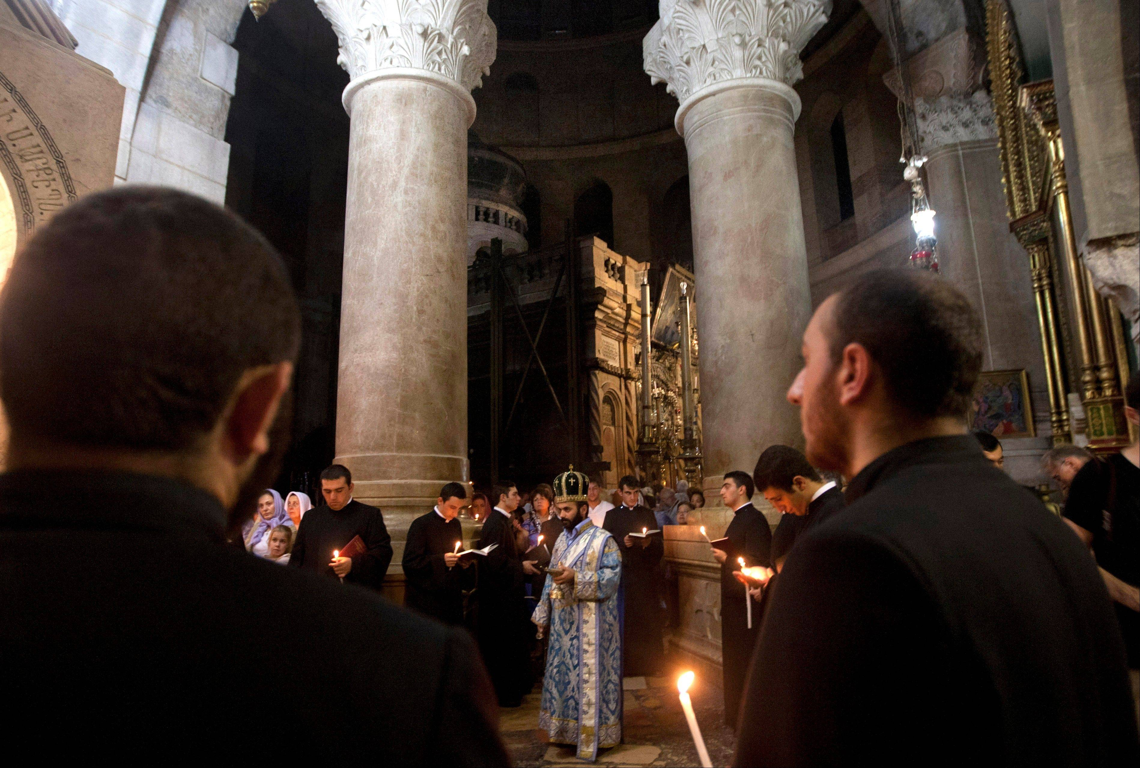 Christian clergymen hold candles Friday inside the Church of the Holy Sepulchre, in Jerusalem�s Old City.