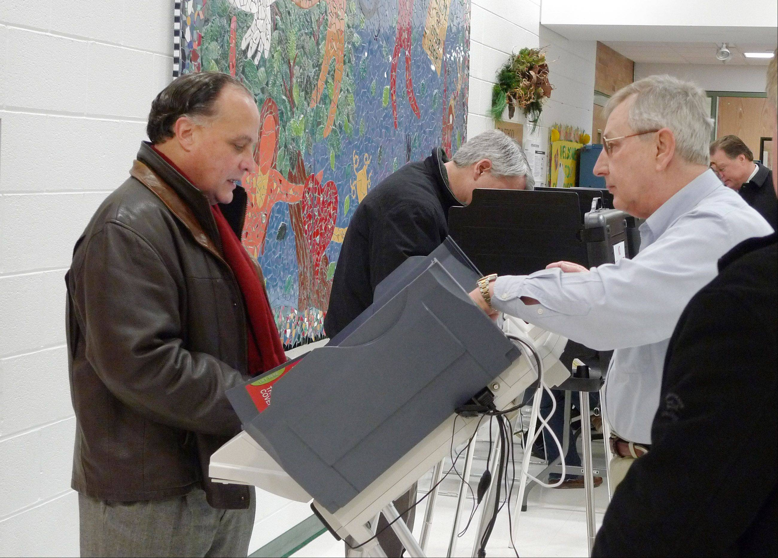 Gary Grasso, left, gets instructions on the workings of the polling place�s single electronic voting machine from election judge John Michalski, right. during the 2010 election.
