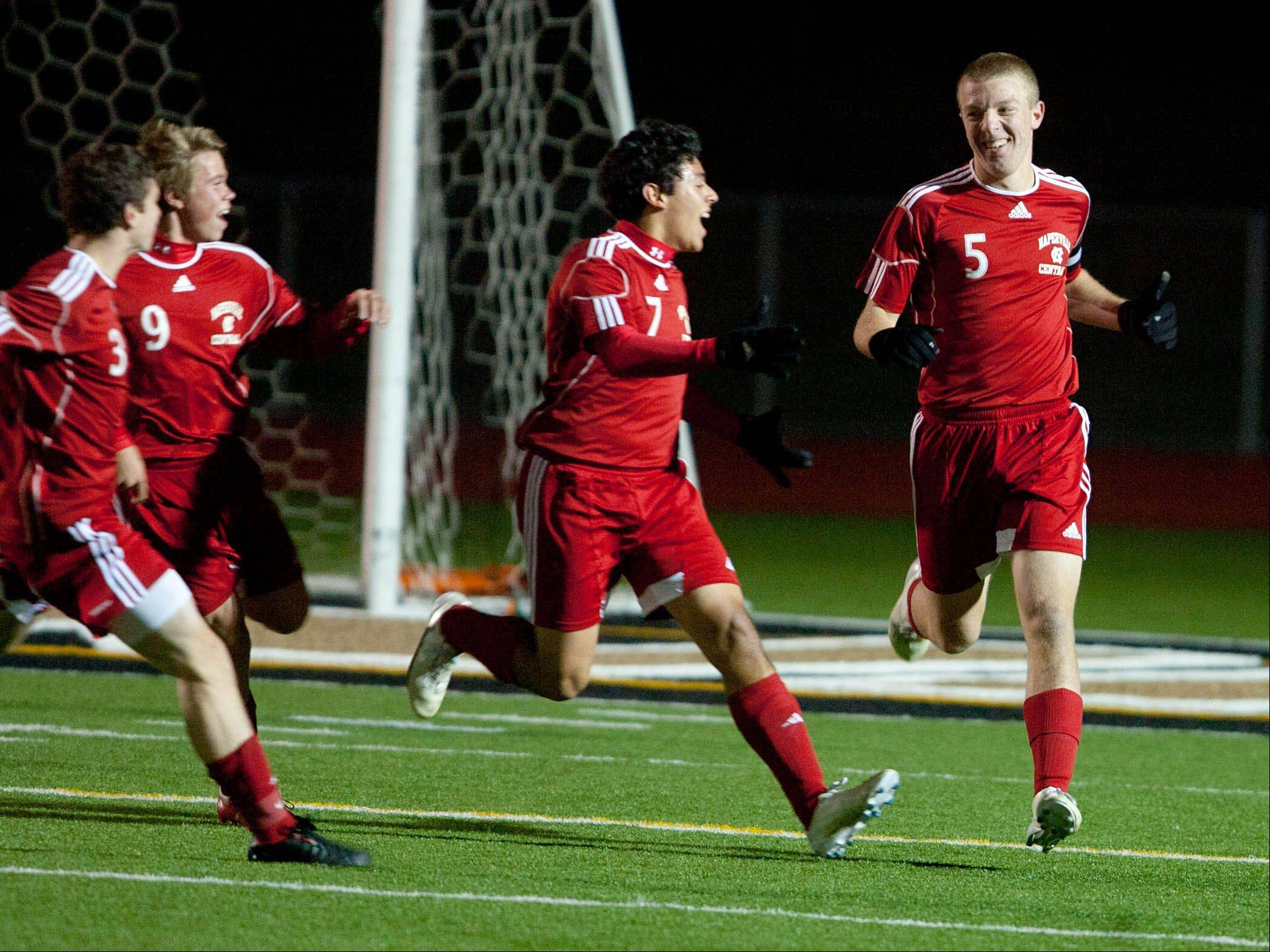 Naperville Central�s Pat Flynn, (5), is congratulated by teammates Jay Tegge (3), Jordi Heeneman (9), and Sam Reskala (7), after scoring the first goal against Stevenson, during the boys 3A state semifinal soccer match held at Lincoln-Way North High School.