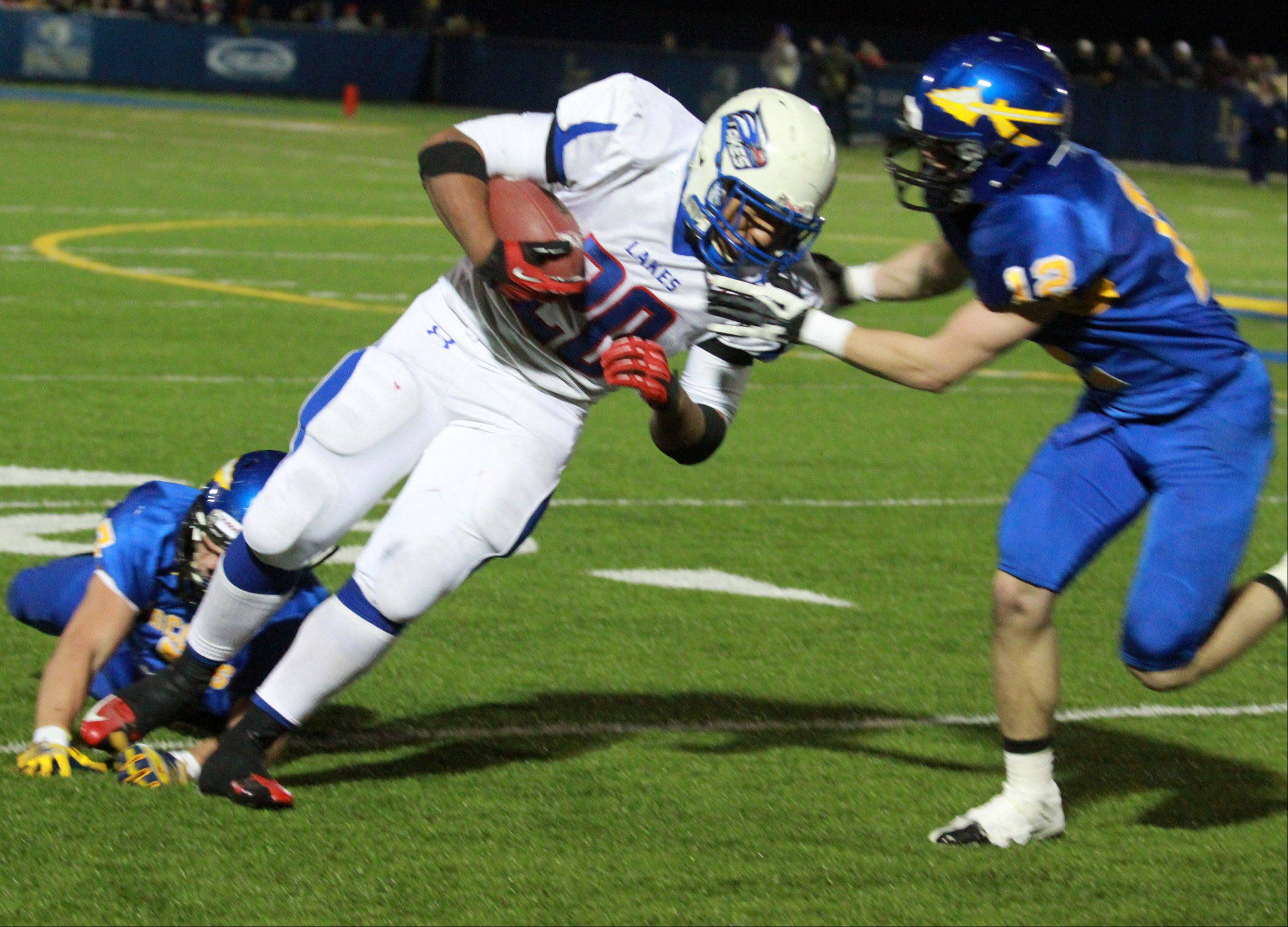 Lakes running-back Direll Clark is pulled down by two Lake Forest defenders late in the fourth quarter.