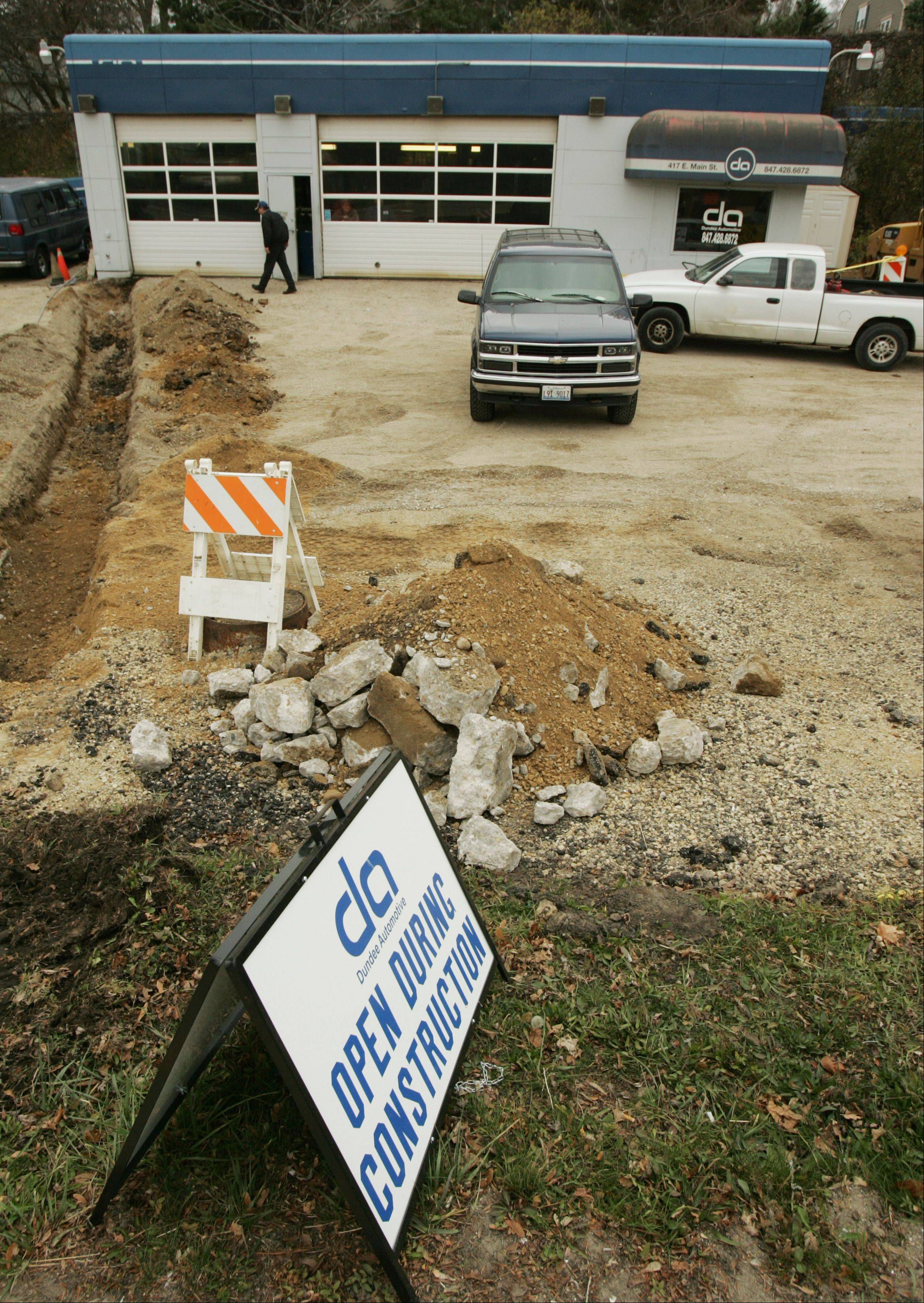 Despite all the work being done to fix the underground water main problem on the property, Dundee Automotive has stayed open in East Dundee. The trench shown here on Monday was dug to install electrical lines and isn't part of the water main repair.