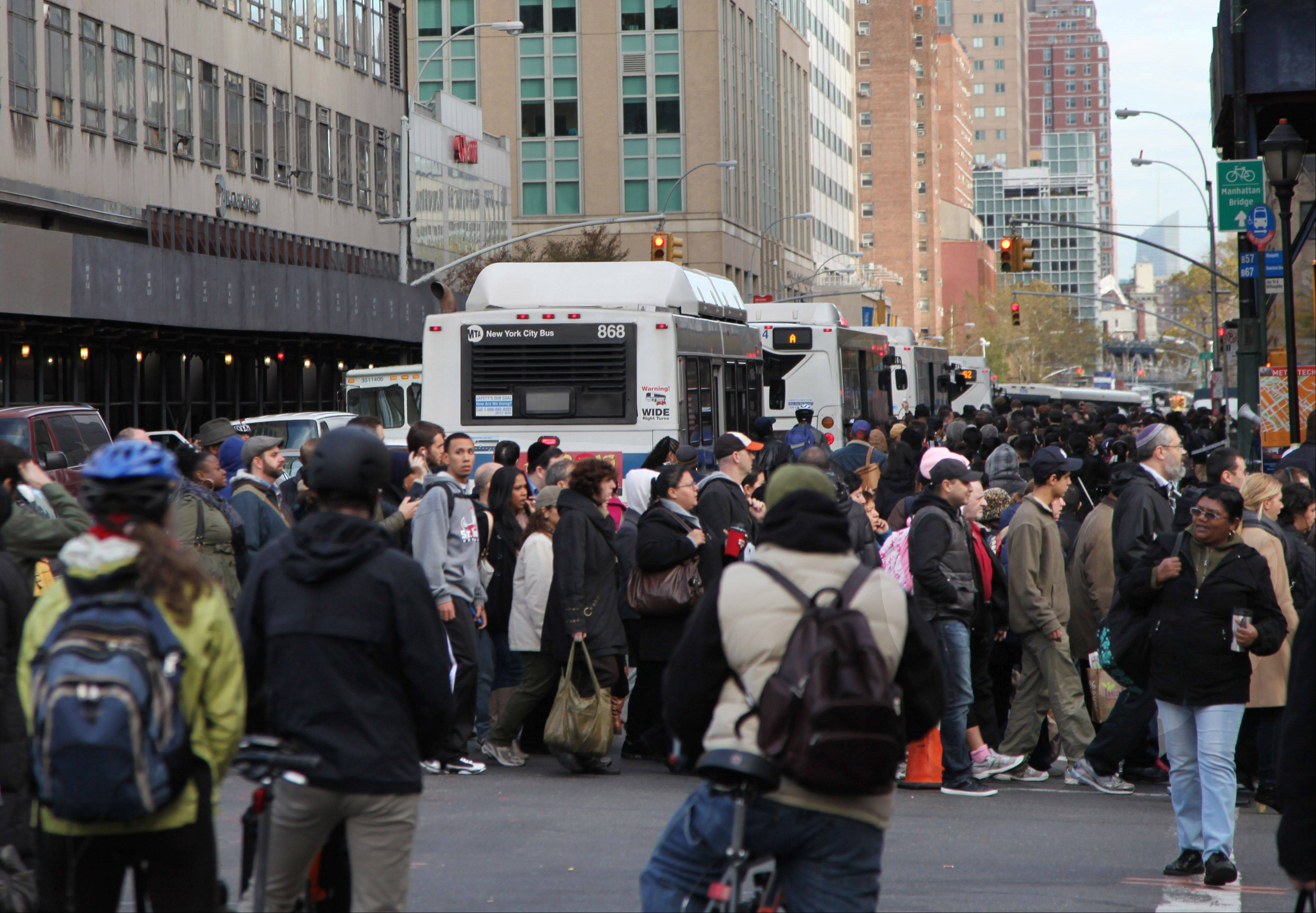 Commuting bicyclists at a stoplight Friday watch a large crowd of people waiting to board special buses into Manhattan near a bus pickup area in Brooklyn.