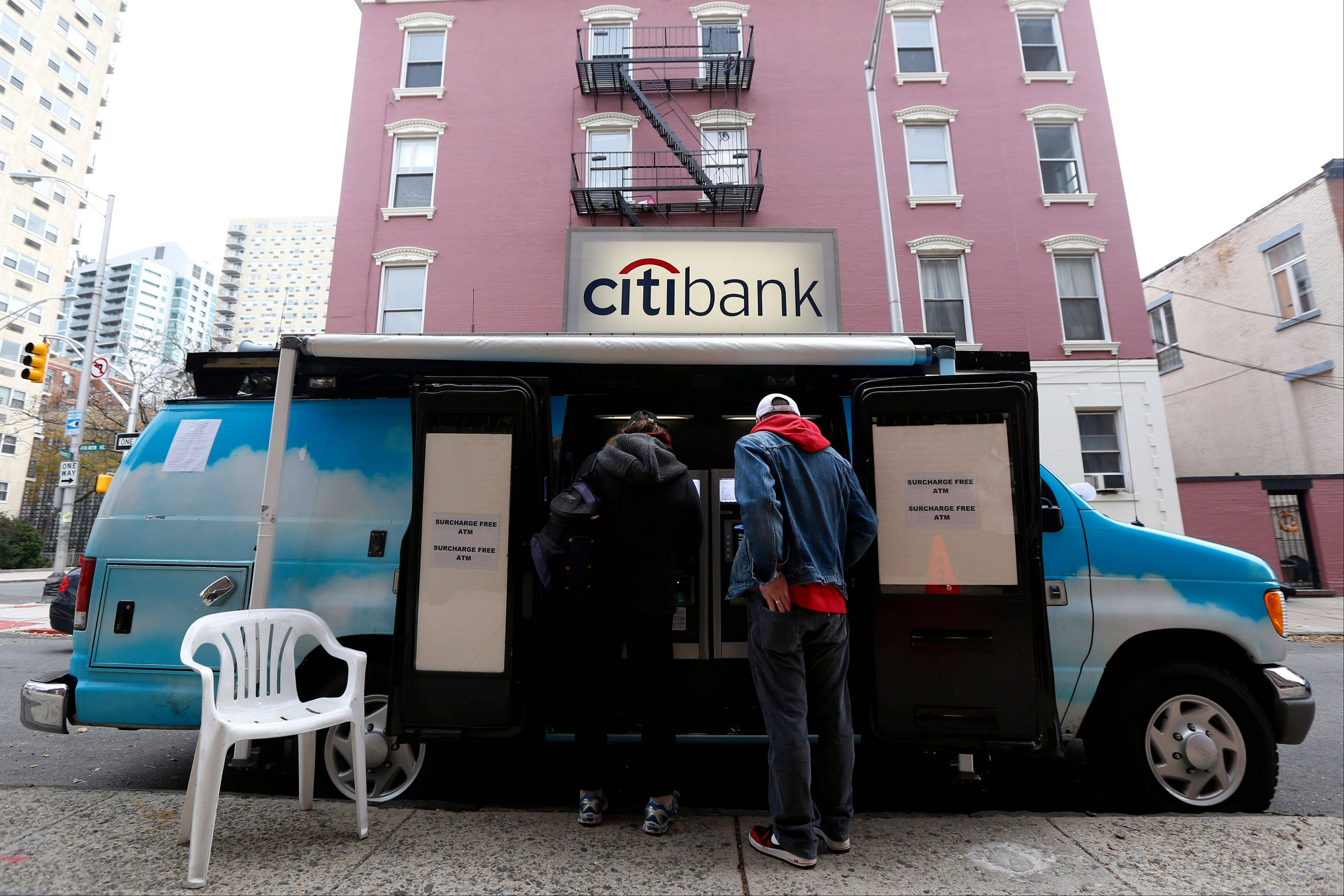 People withdraw money Friday from a mobile ATM machine set up in a van in Hoboken, N.J. The mobile ATM gives residents a chance to get cash in Hoboken, which is still blacked out following Superstorm Sandy.