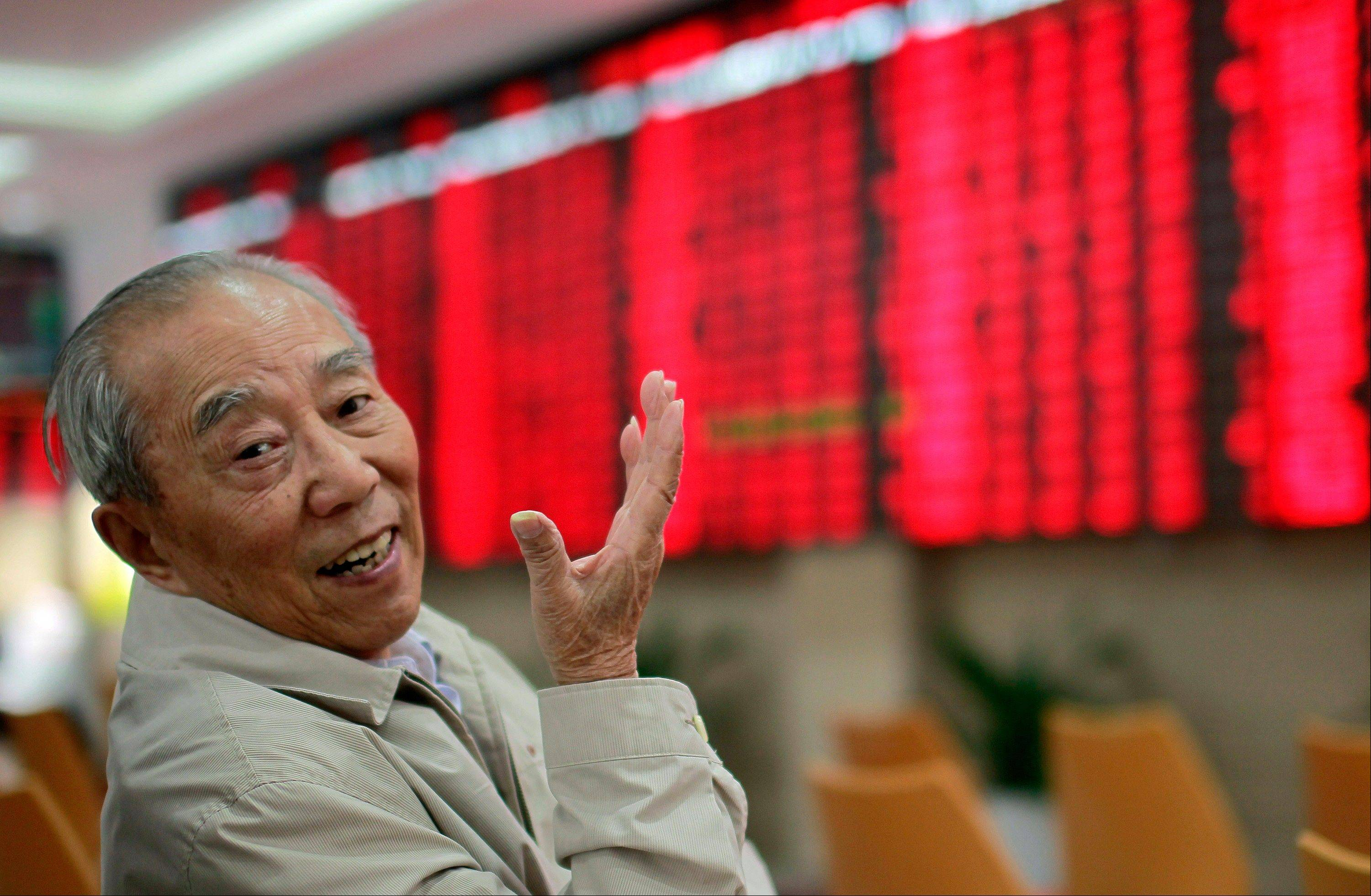 An investor gestures as he monitors the stock prices at a private securities company Thursday in Shanghai, China.