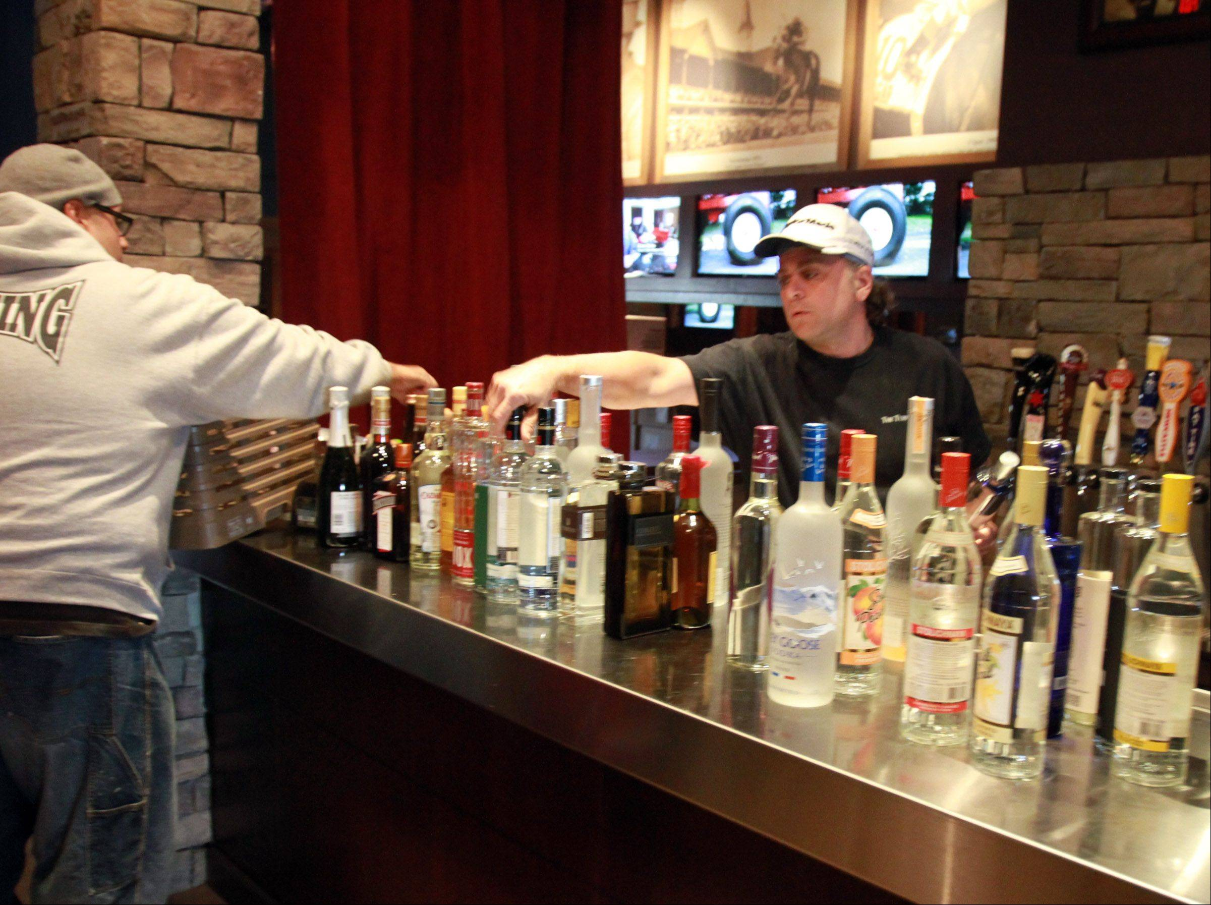 The Saddle Room co-owner Parker Grabowski, right, and server/bartender Porfirio Salamanca prepare the bar area of the new off-track betting restaurant for its opening Friday at 2559 Pratum Ave. in Hoffman Estates.