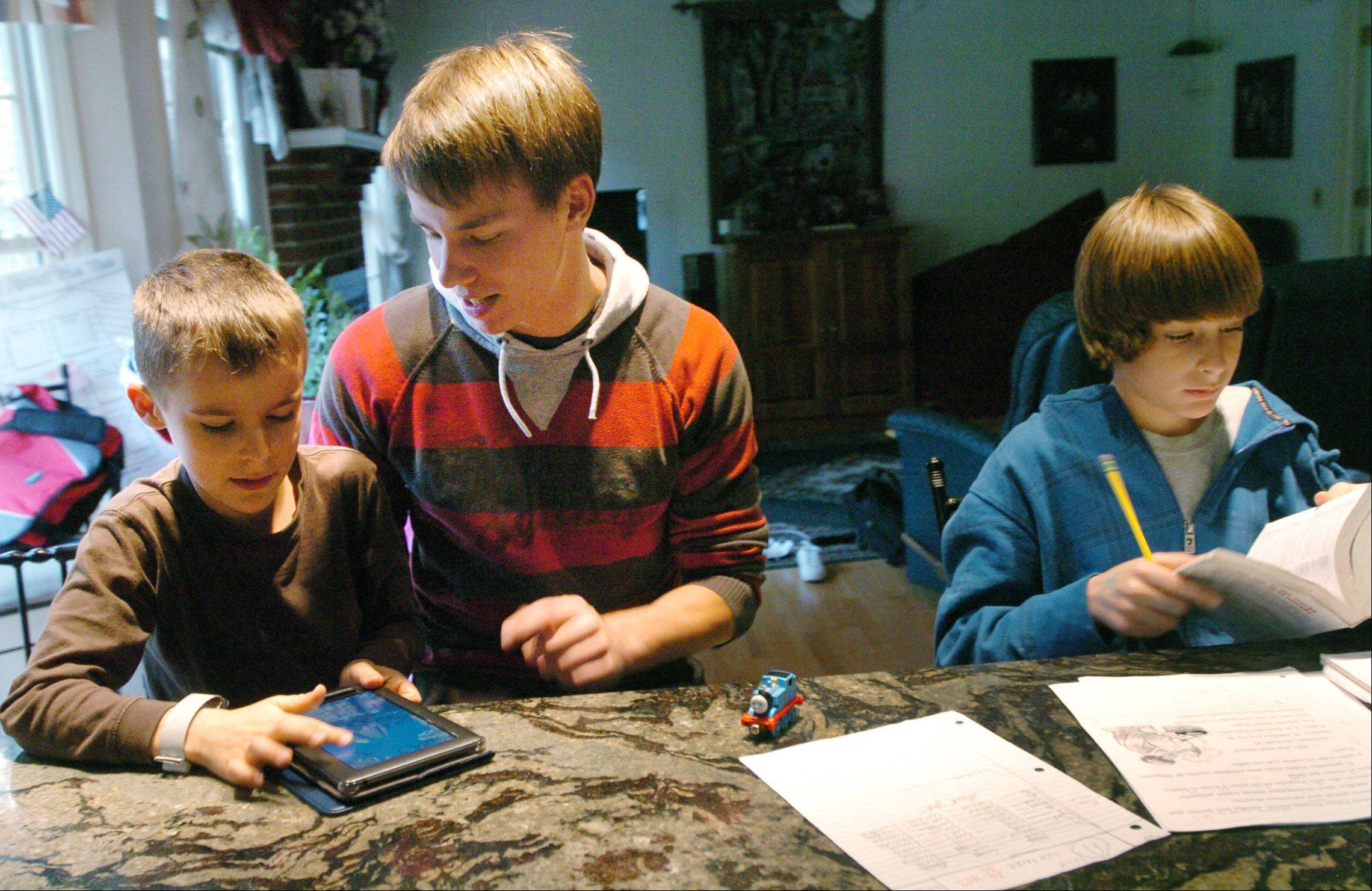 German au pair Julian Bucker works on homework with Sawyer, left, and Drayce Adams of Gurnee.