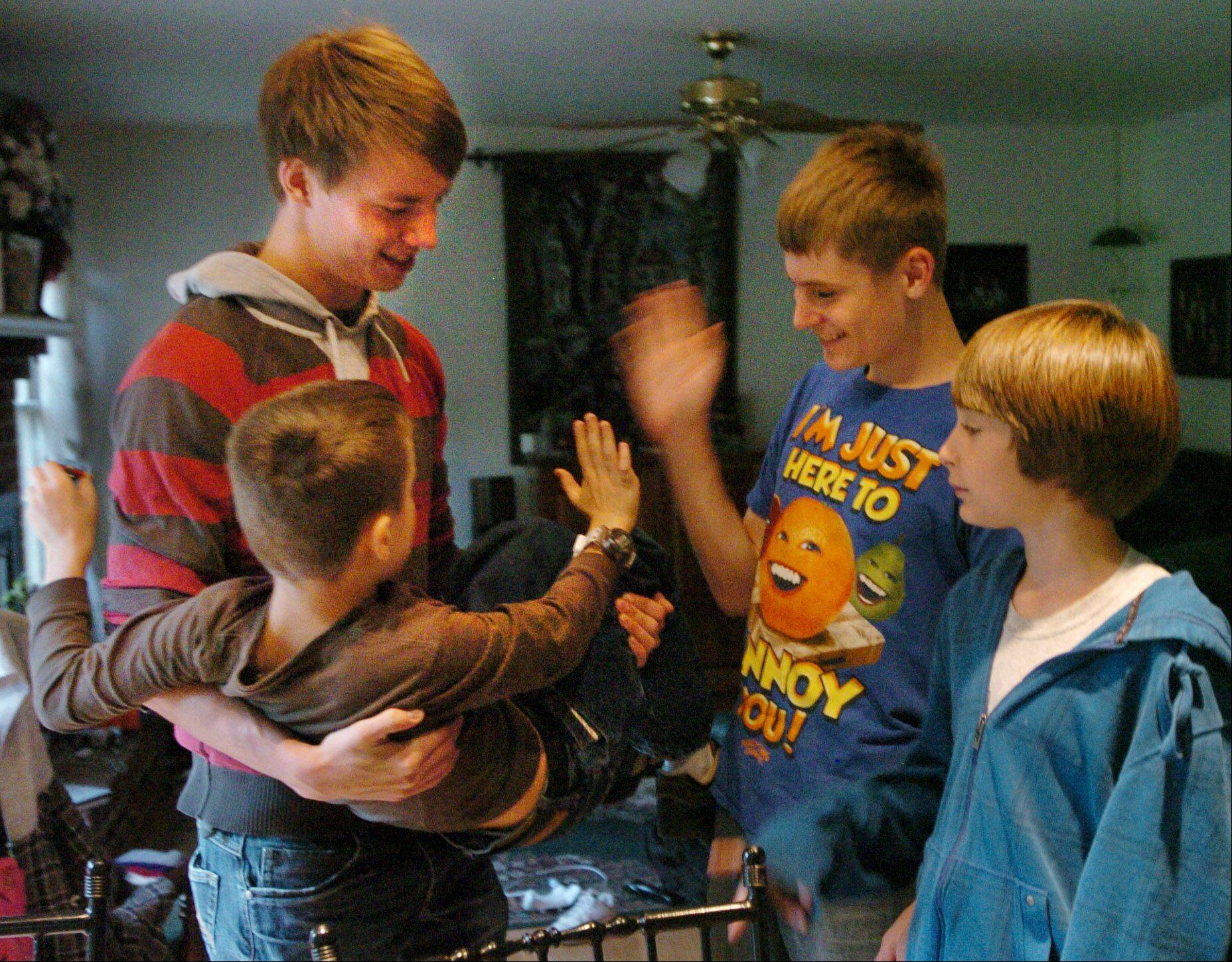 German au pair Julian Bucker plays with Sawyer, Logan and Drayce Adams of Gurnee.
