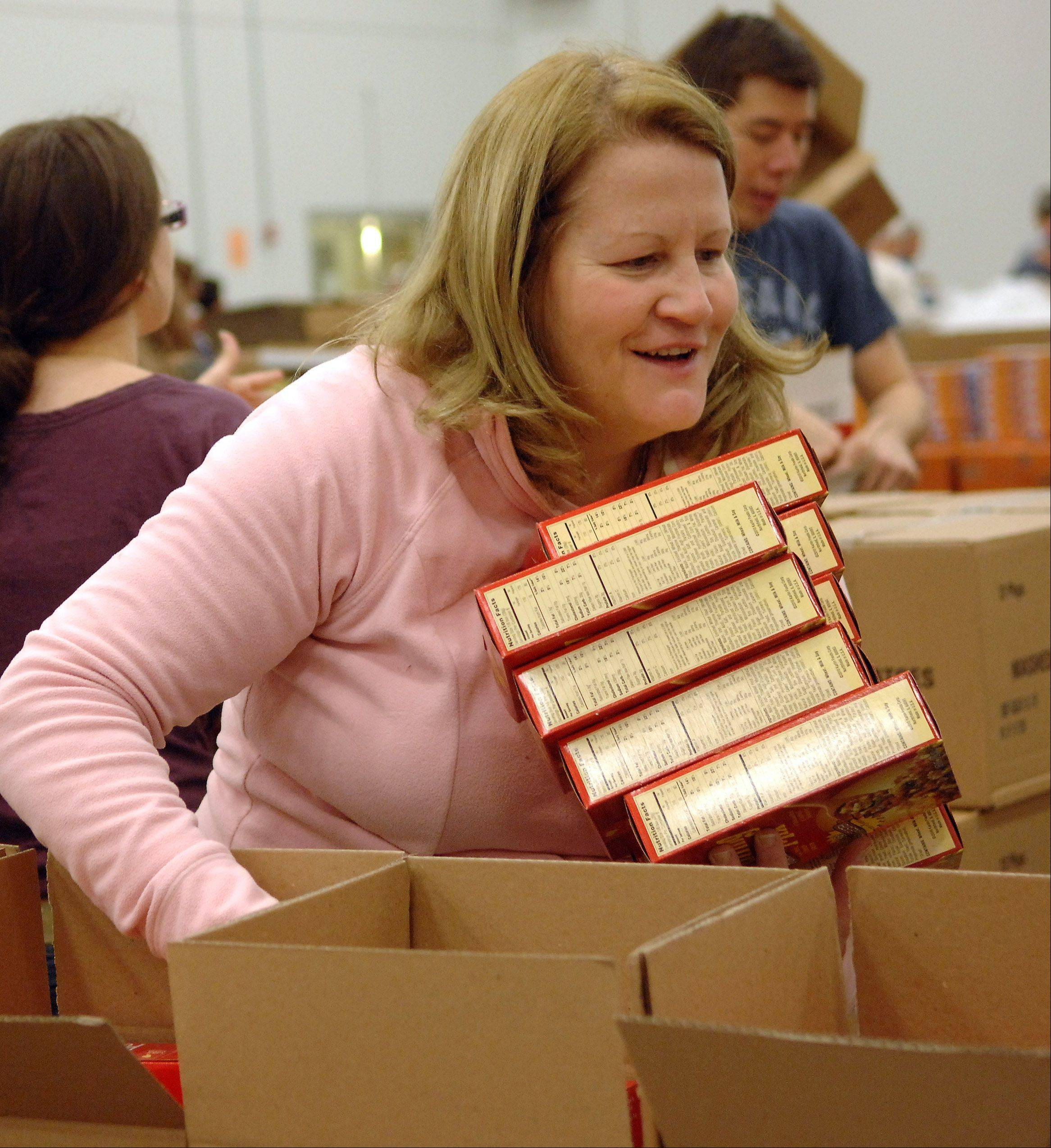 Sheila Creghin of Oak Lawn carries an armful of stuffing as more than 100 volunteers from Jewel-Osco pack boxes of holiday meals Saturday at the Northern Illinois Food Bank in Geneva. The food bank plans to prepare more than 30,000 holiday meal boxes for those in need this season.