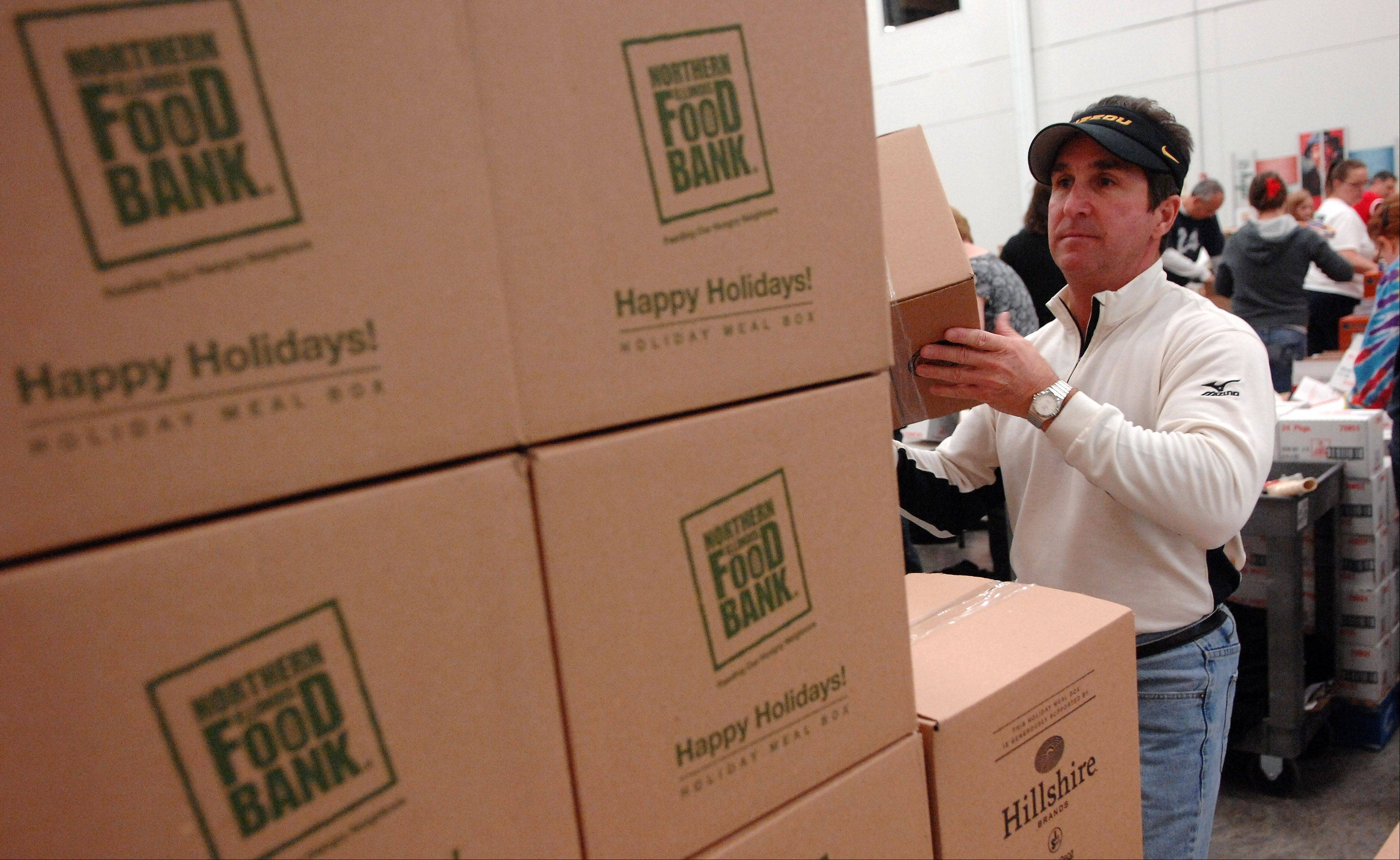 Jim Bolin of Plainfield and more than 100 other volunteers from Jewel-Osco pack boxes of holiday meals Saturday at the Northern Illinois Food Bank in Geneva. The event was one of the first in a six-week program during which the food bank will pack more than 30,000 holiday meals for the less fortunate.