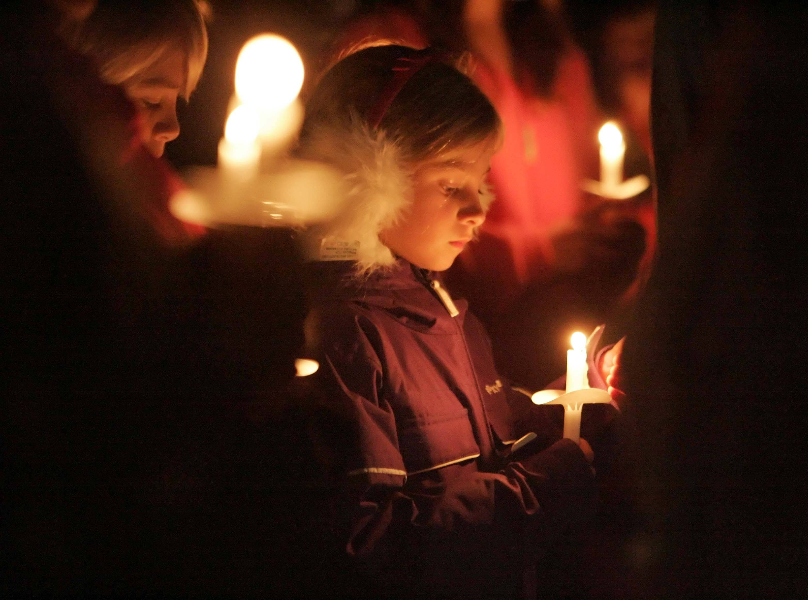 A girl named Lucy pauses during a moment of silence during a vigil Friday night for 5-year-old Olivia Dworakowski at St. Thomas the Apostle Catholic Church in Naperville.